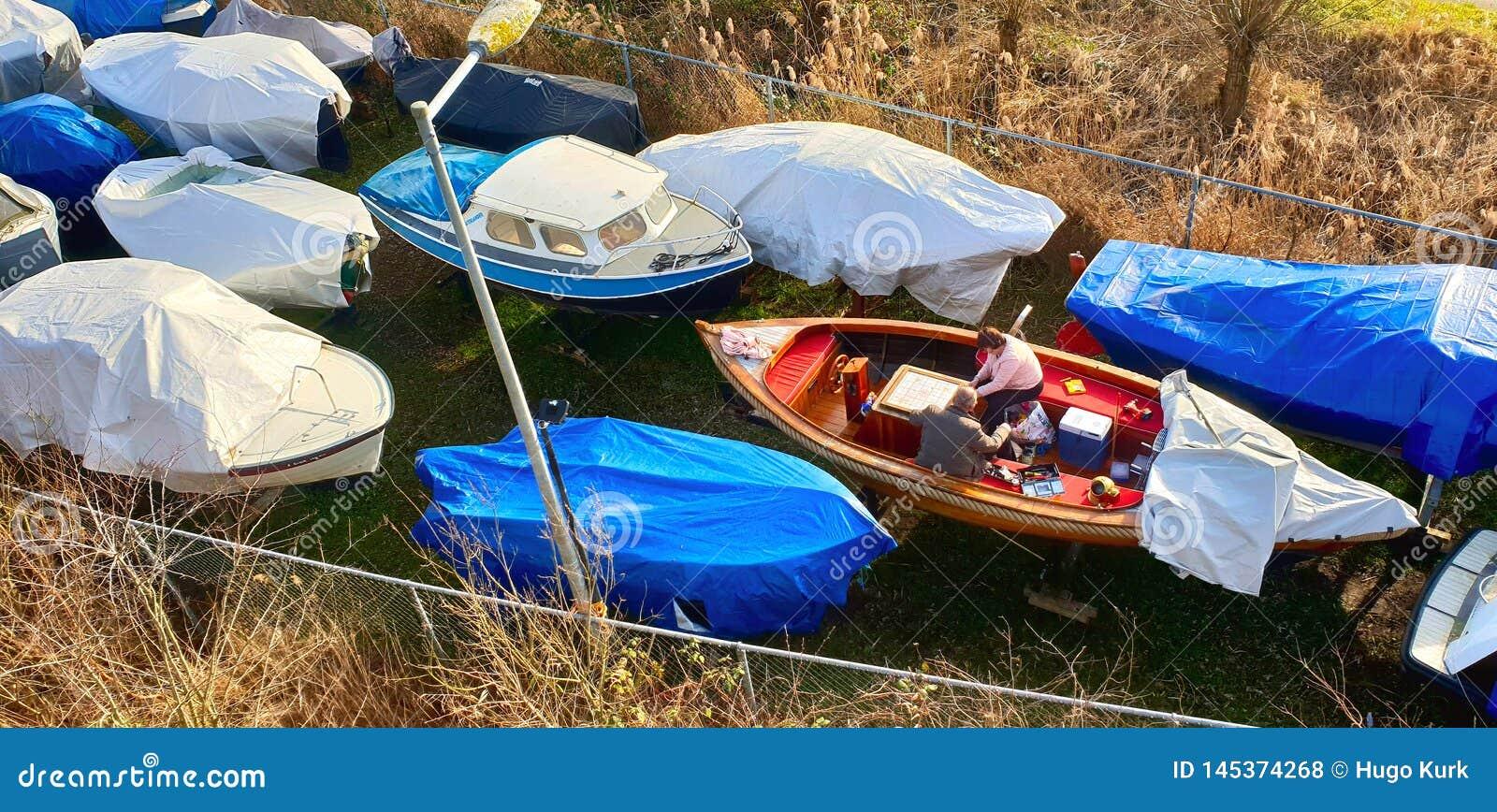 Amsterdam, Holandia holandie,/- 02-17-2019 Dwa persons przygotowywa łódź dla nowego wiosny i lata sezonu
