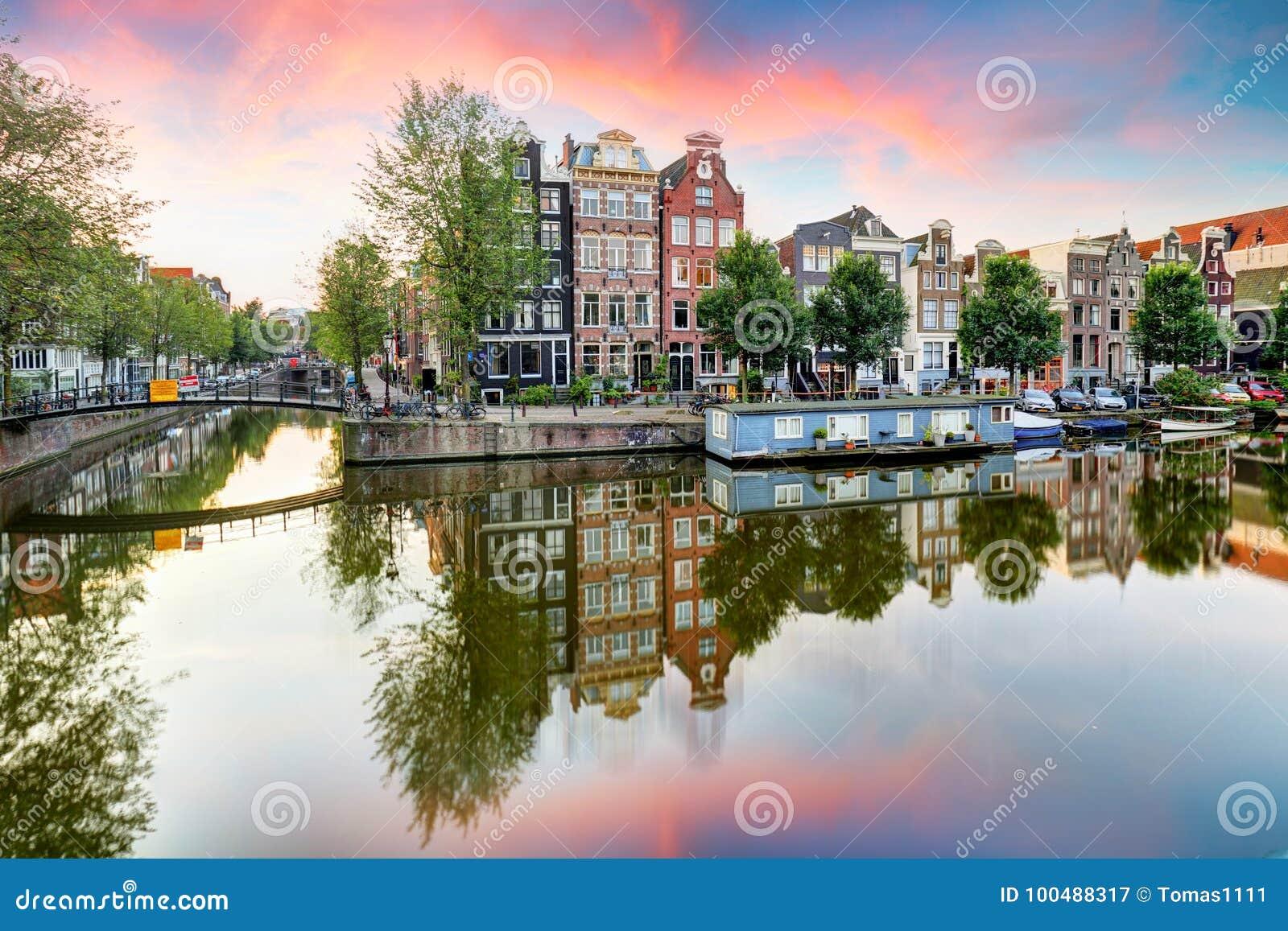Amsterdam kanału domy przy zmierzchów odbiciami, holandie