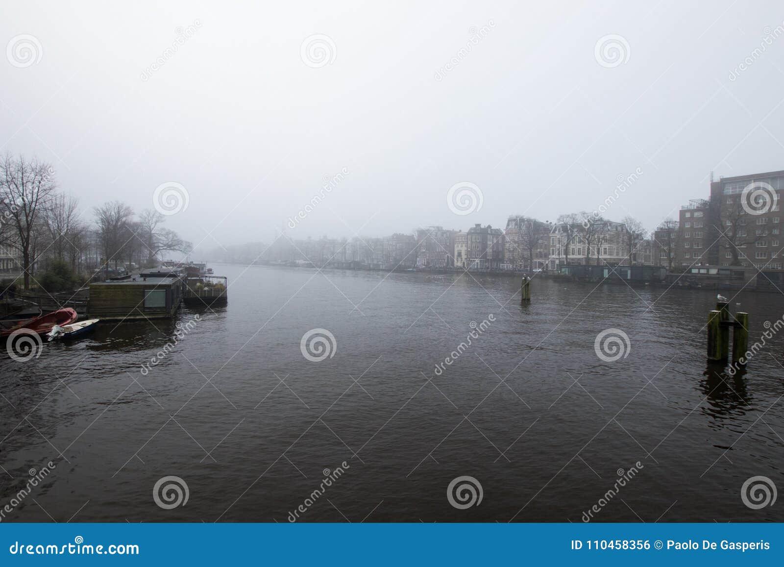 Amsterdam kanal med dimma Dag med mycket dimma i en Amsterdam