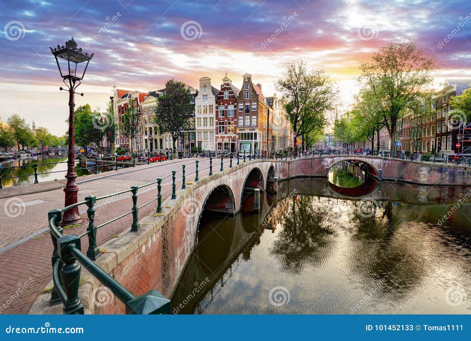 Amsterdam kanalhus på solnedgångreflexioner, Nederländerna