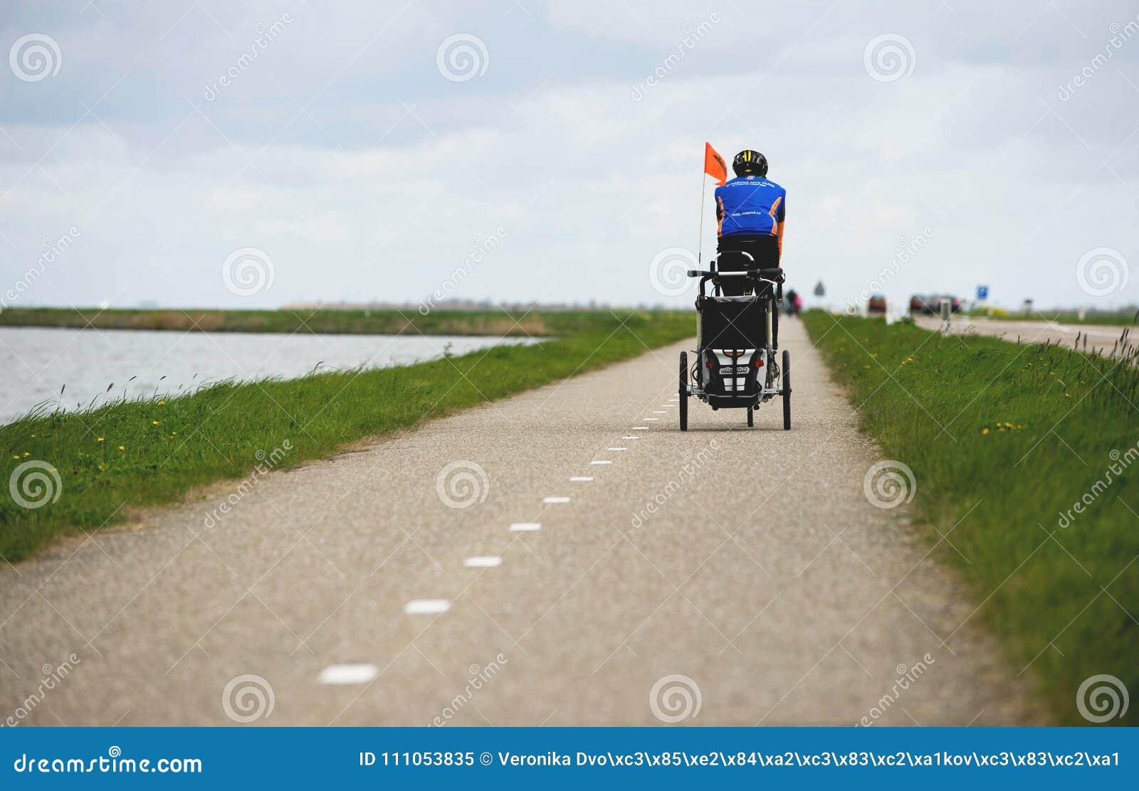 AMSTERDAM NEDERLÄNDERNA, April 2017: Mannen på dra för cykel behandla som ett barn vagnen för en cykeltriumfvagn vid Thule Cykelb