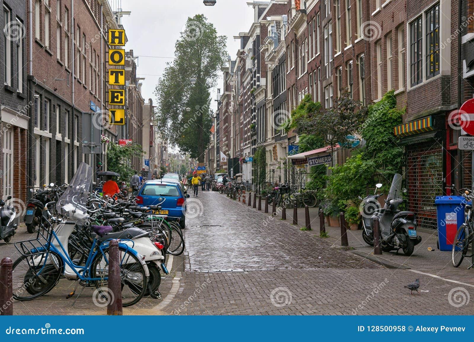 AMSTERDAM, NEDERLAND - JUNI 25, 2017: Weergeven van één van de stadsstraat onder de regen in het historische deel