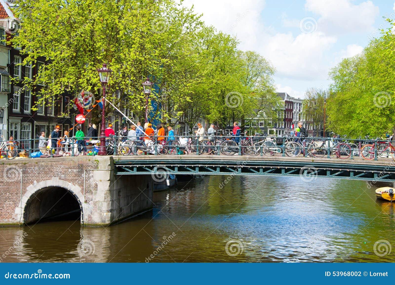 AMSTERDAM NETHERLANDS-APRIL 27: Amsterdam kanal med folkmassan av folk på bron och cyklarna på konungs dag i Amsterdam