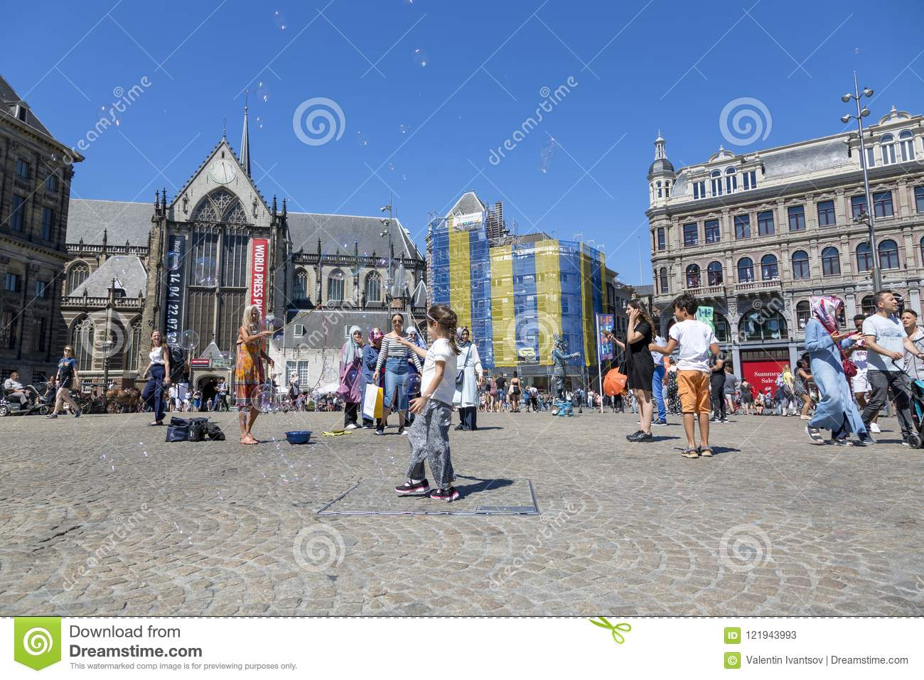 Children catch soap bubbles in the central Dam Square in Amsterdam