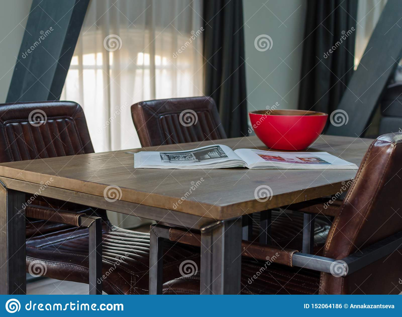 Amsterdam Netherlands May 2019 Wood And Metal Dining Table With Cozy Leather Chairs Wooden Red Bowl And Open Magazine In A Stock Photo Image Of Amsterdam Chair 152064186