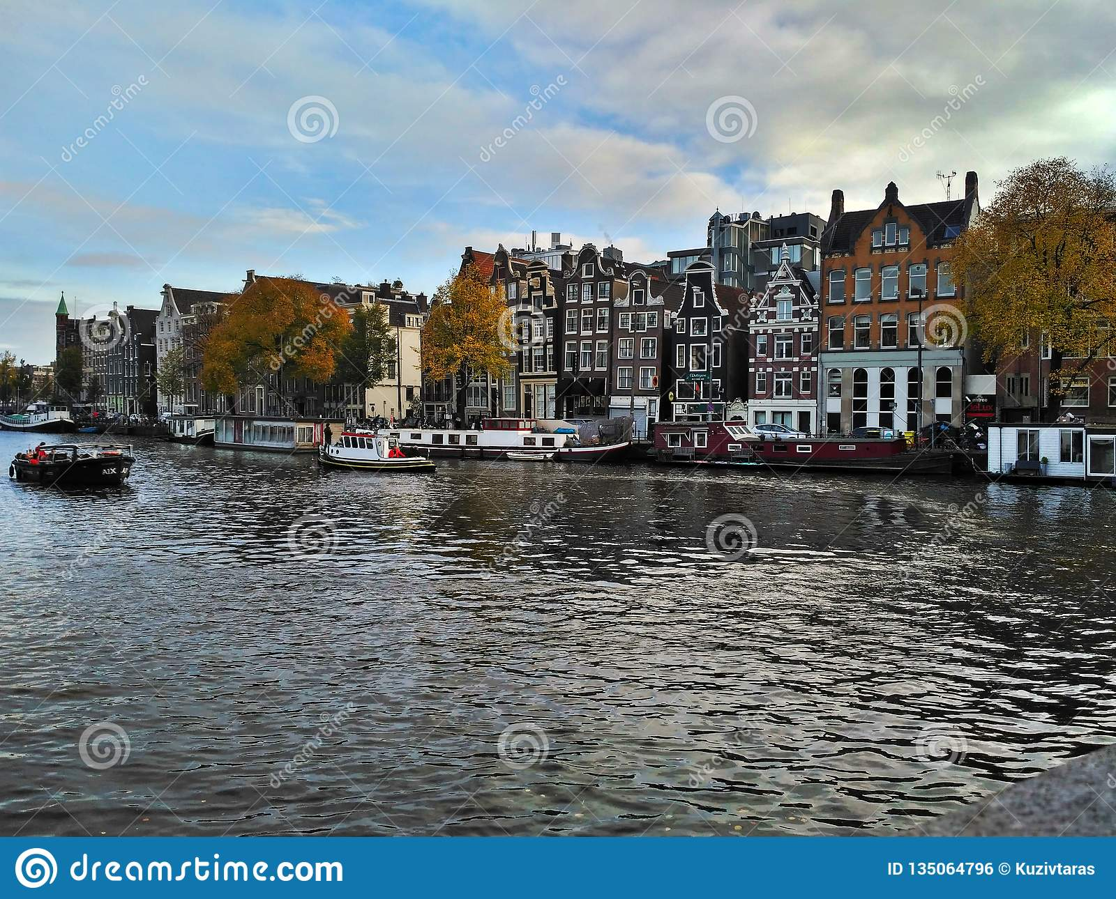 Amsterdam / The Netherlands - October 30 2016: View on Amsterdam canal, boats and traditional dutch houses
