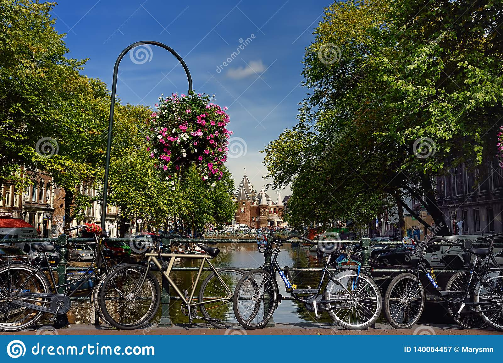 AMSTERDAM, NETHERLANDS - SEPTEMBER 17, 2018: Street, canal, bridge with bicycles, Nieuwmarkt New market building on background