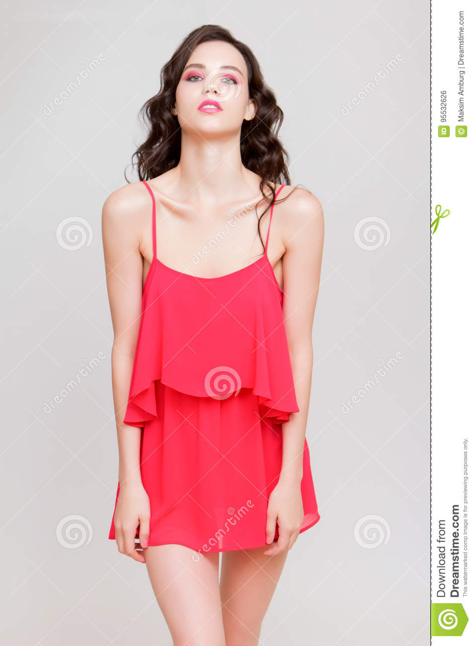 Amused beautiful young woman in pink mini dress posing on hip and looking