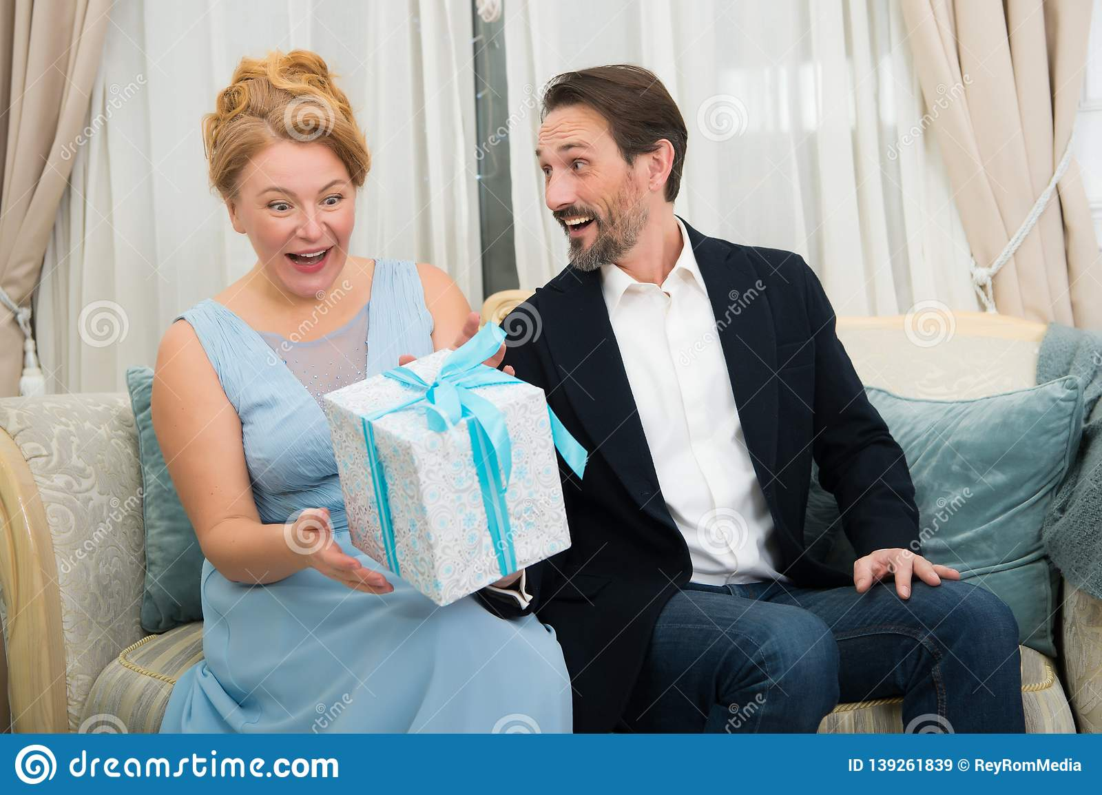 Amused charming woman expressing happiness while receiving a present from her beloved husband