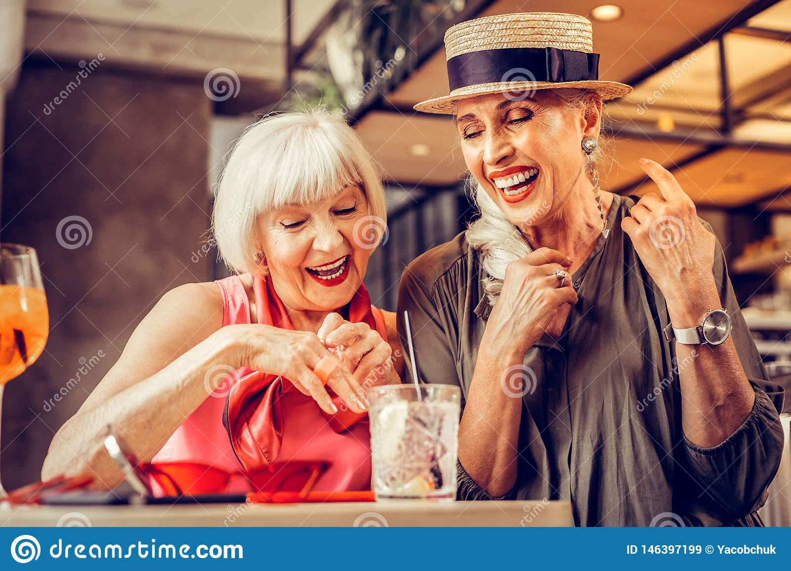 Amused good-looking old ladies being excited while drinking together