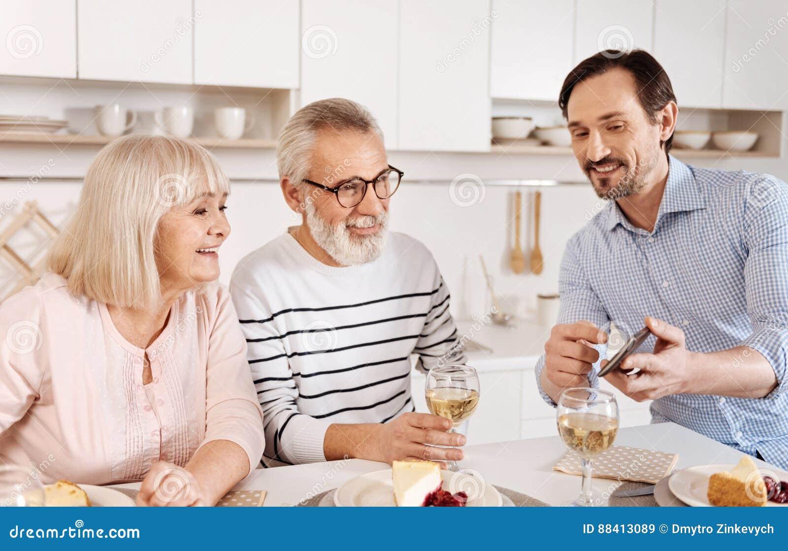 Amused mature man enjoying family weekend at home