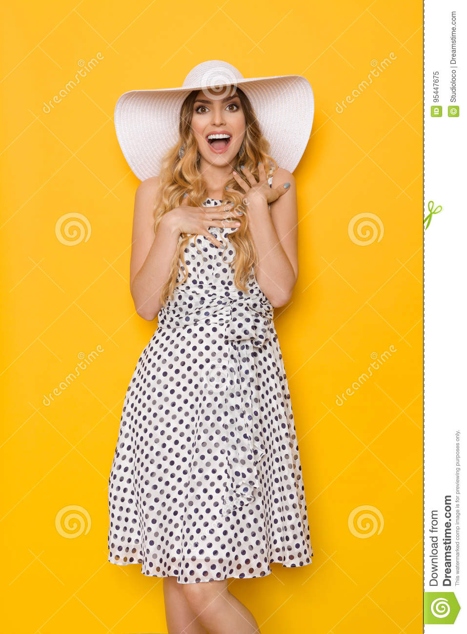 7cbe61e90381 Beautiful young woman in white dotted summer dress and sun hat is holding  hands on chest