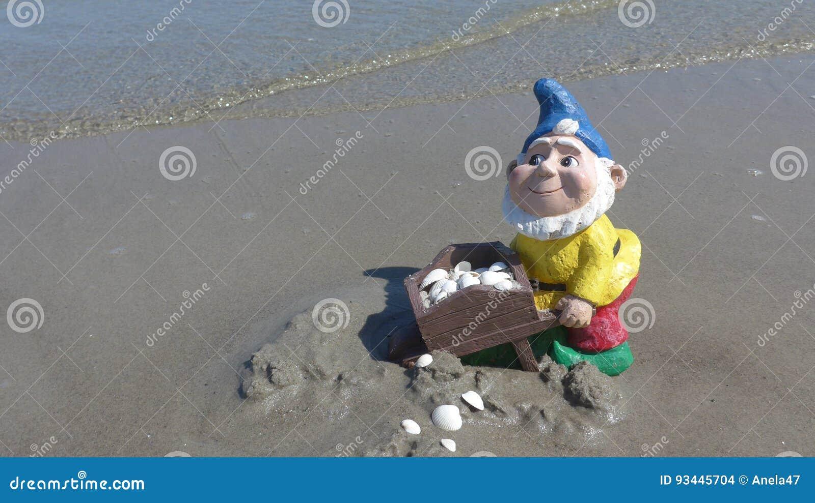 Anão engraçado do jardim com o carrinho de mão na praia