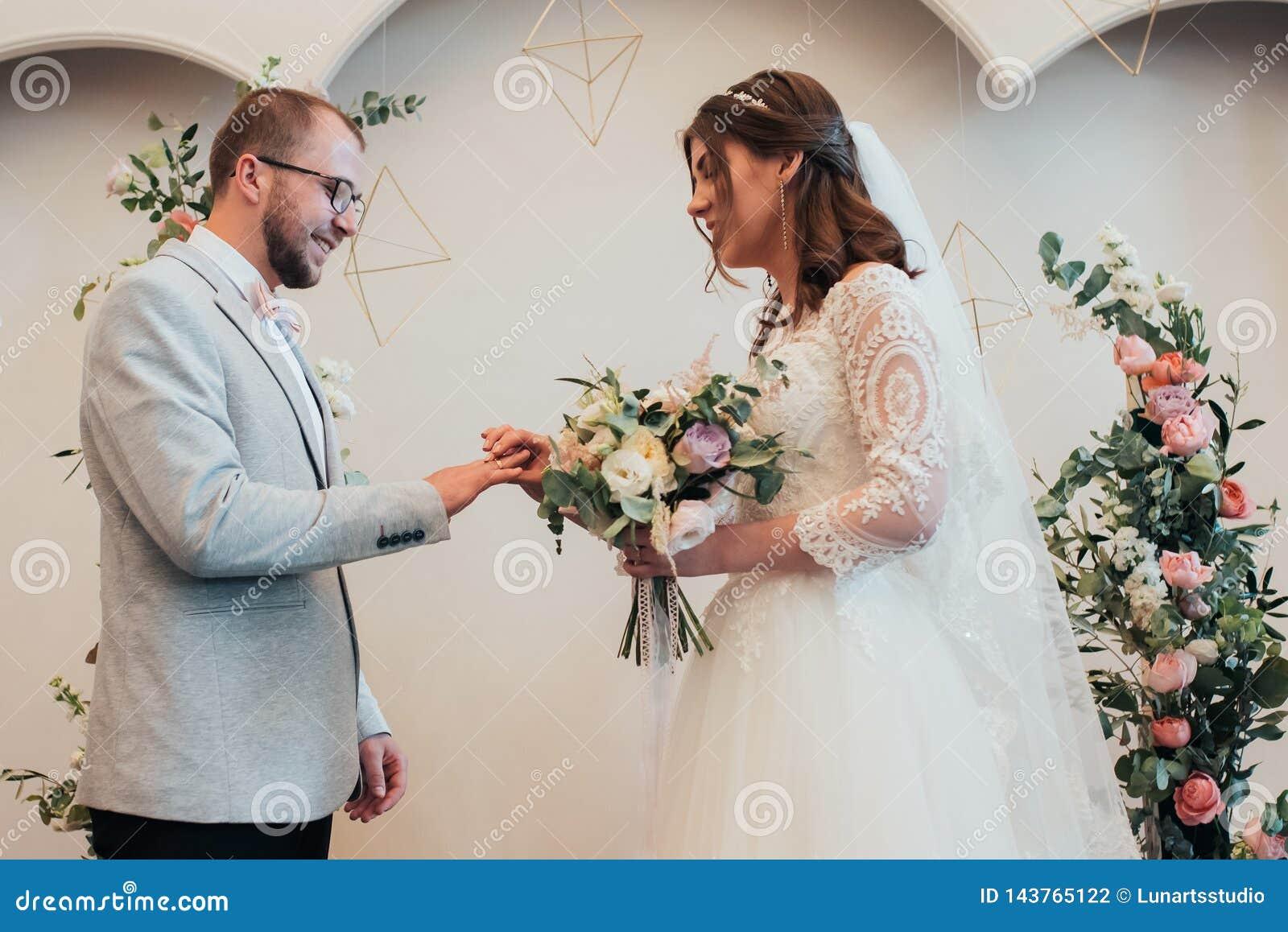 Anéis de ouro do casamento da troca dos noivos