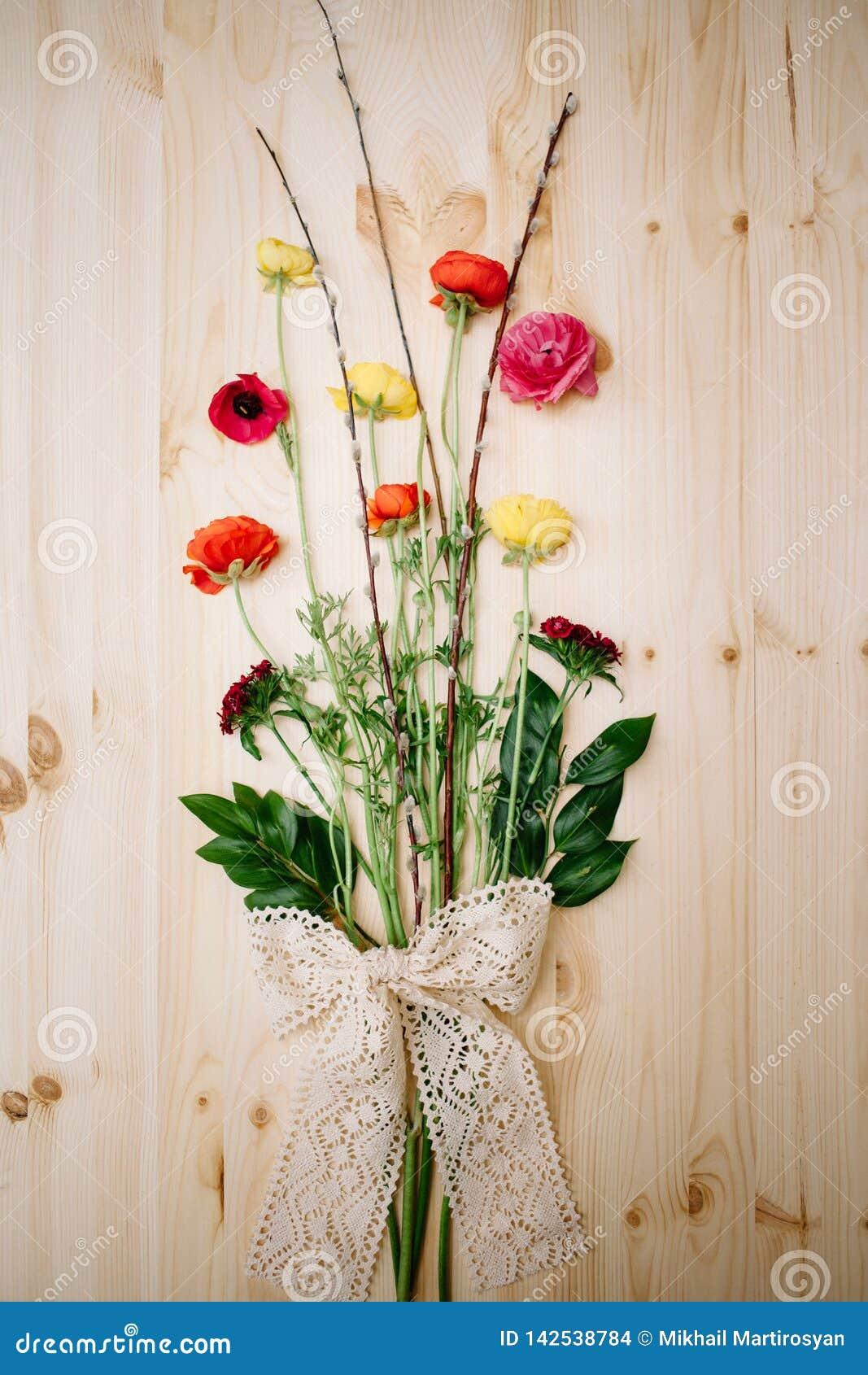 Anêmonas e salgueiro das flores da mola em um fundo de madeira amarrado com fita do laço