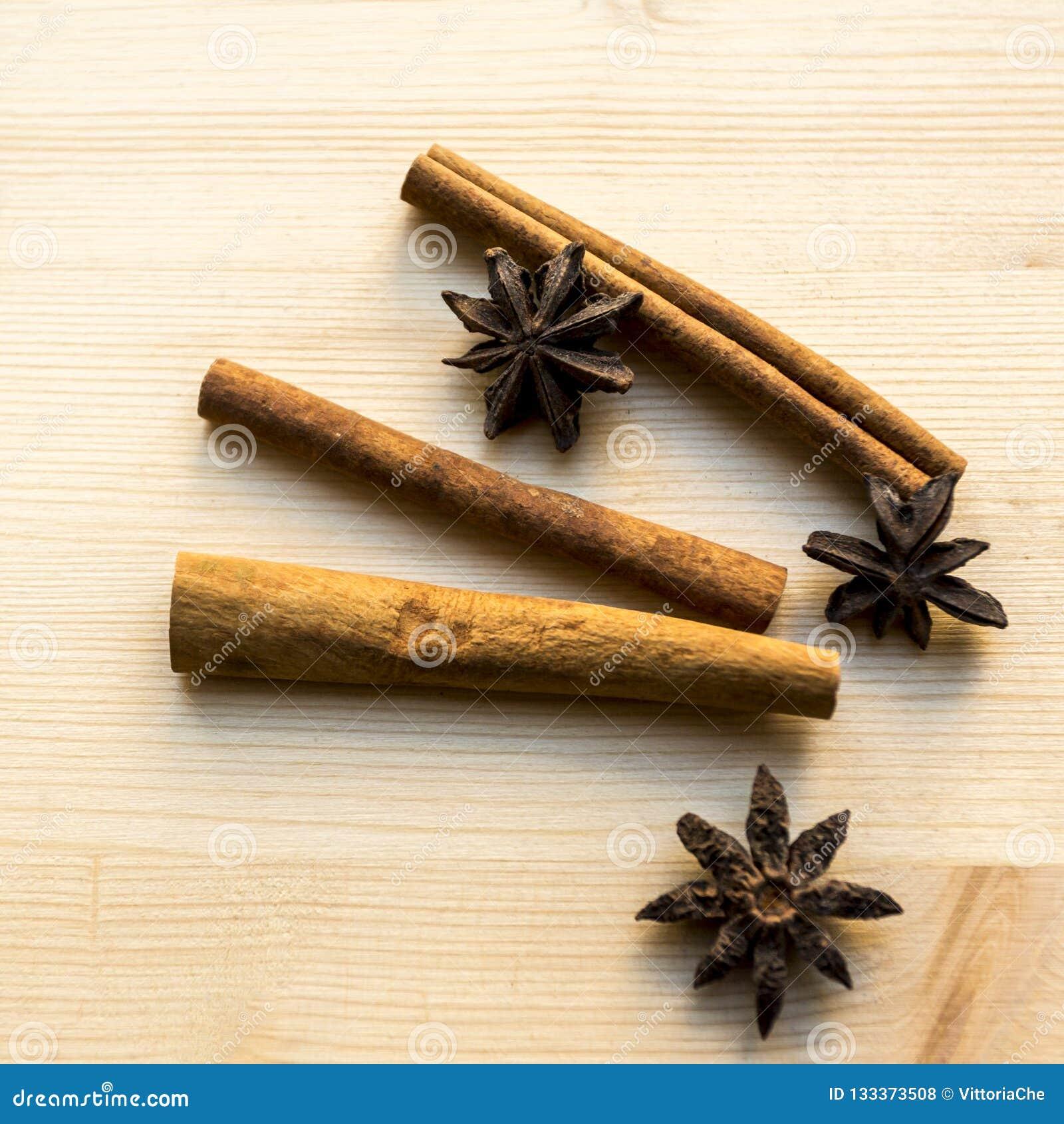 Anís y palillos del canela en fondo de madera Especias para el café, té caliente, vino reflexionado sobre, sacador