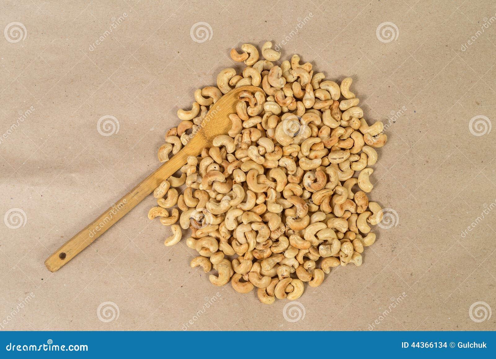 Anacardii arrostiti su carta con il cucchiaio di legno