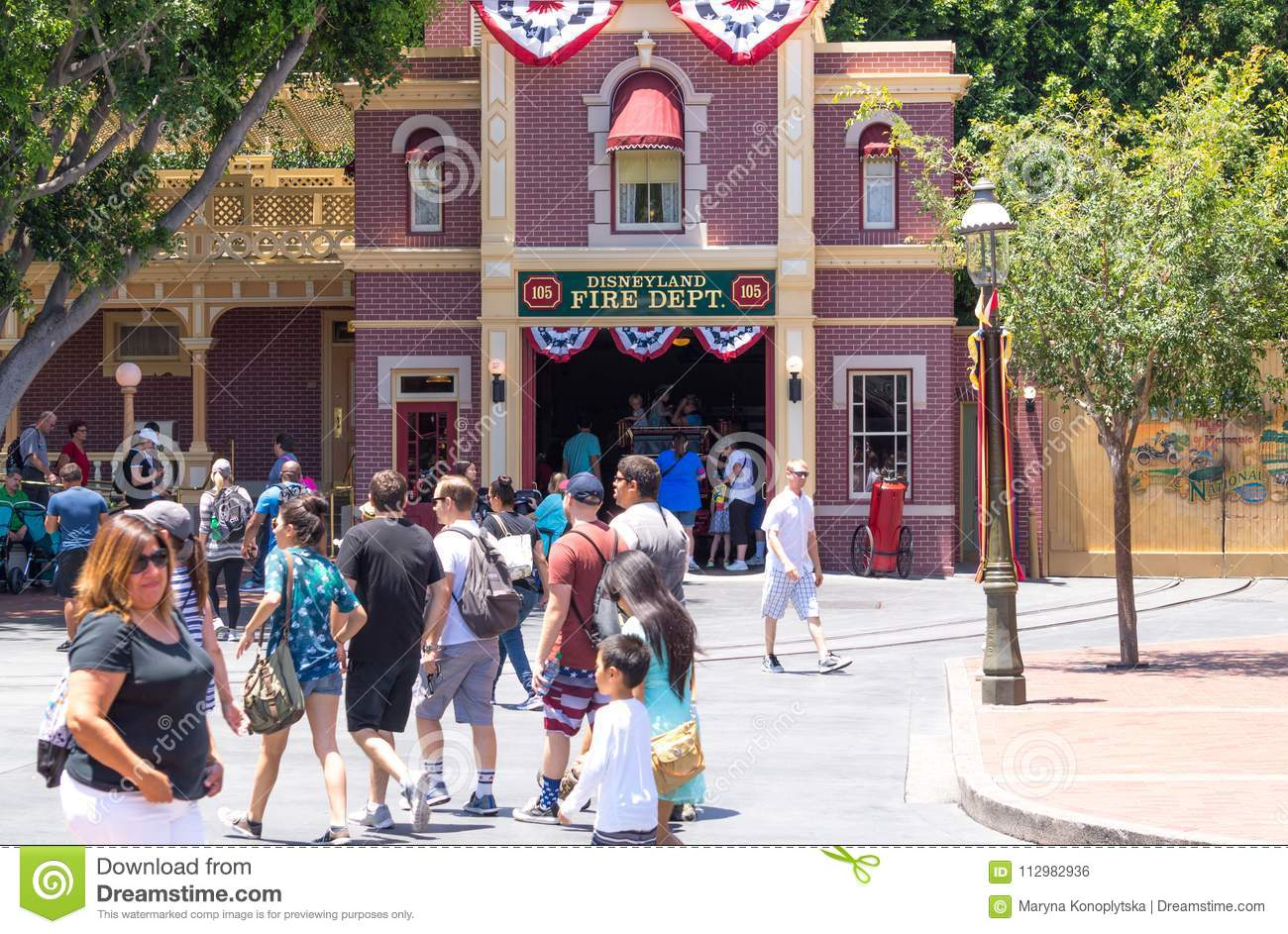 Colorful architecture of the Disneyland Park in Anaheim, Los Angeles, California, USA. People on an entertaining walk