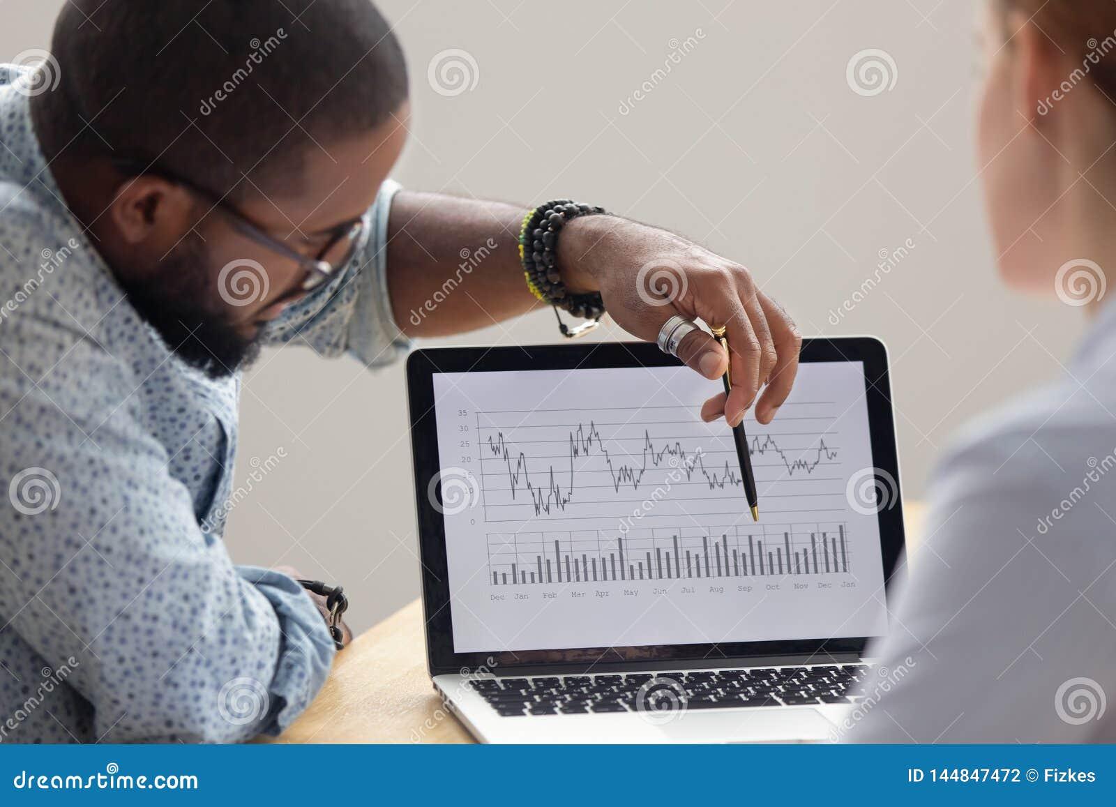 Analista africano messo a fuoco che mostra rapporto finanziario annuale sullo schermo del computer portatile