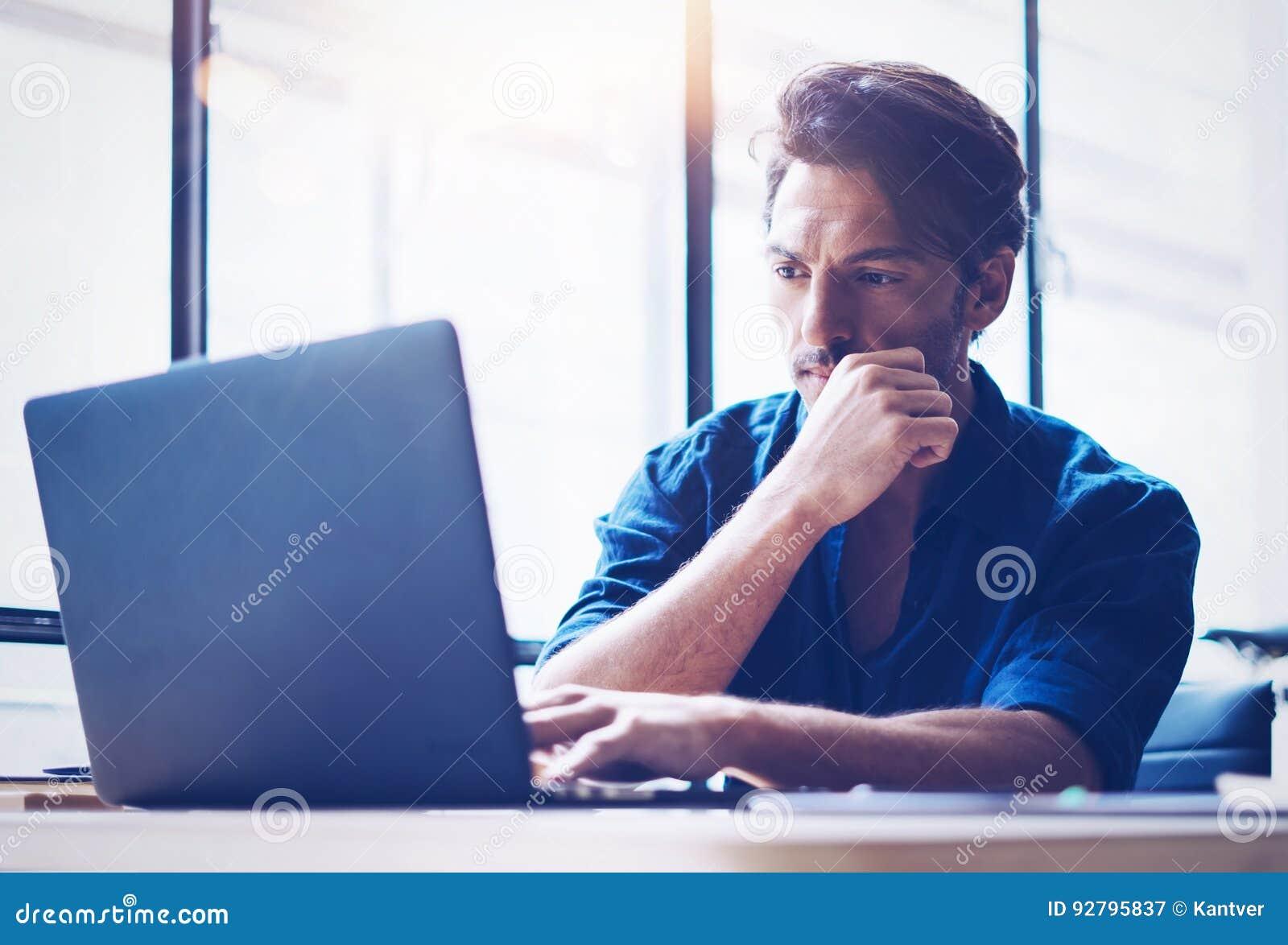 Analista considerável novo da finança da operação bancária que trabalha no escritório ensolarado no portátil ao sentar-se na tabe