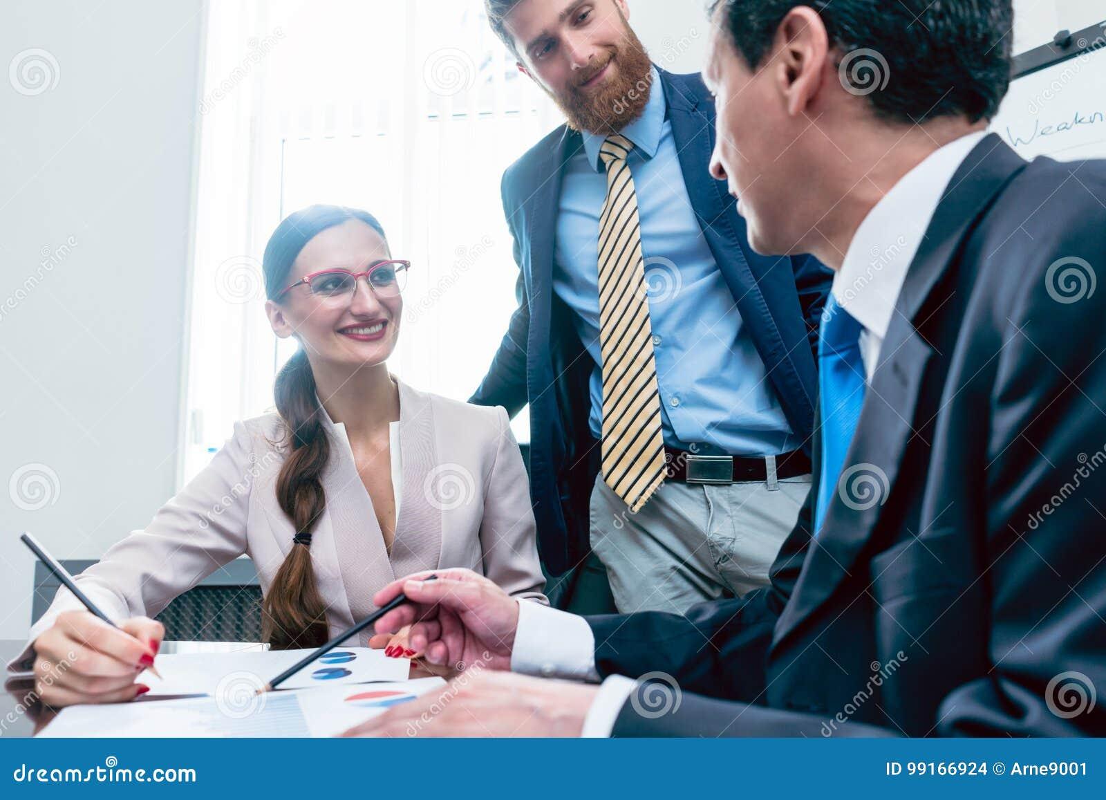 Analista do negócio que sorri ao interpretar os relatórios financeiros sh
