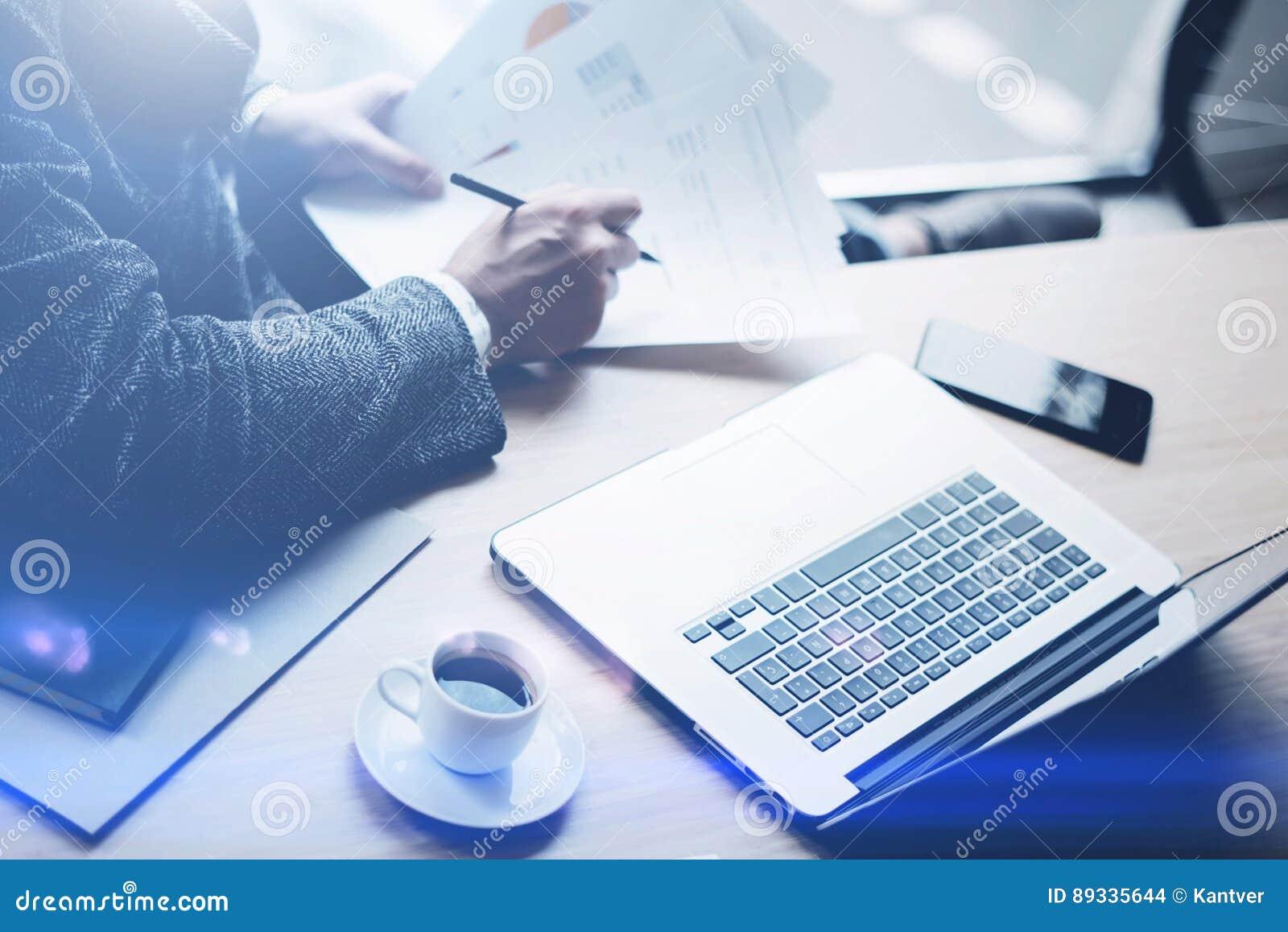 Analista elegante da finança da operação bancária que trabalha no escritório ensolarado no portátil ao sentar-se na tabela de mad