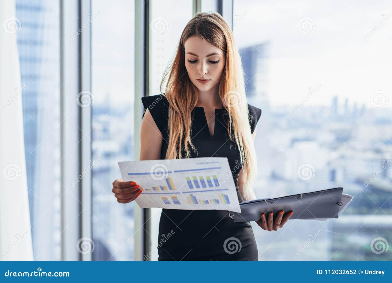 Analista financeiro fêmea que guarda os papéis que estudam os originais que estão contra a janela com opinião da cidade