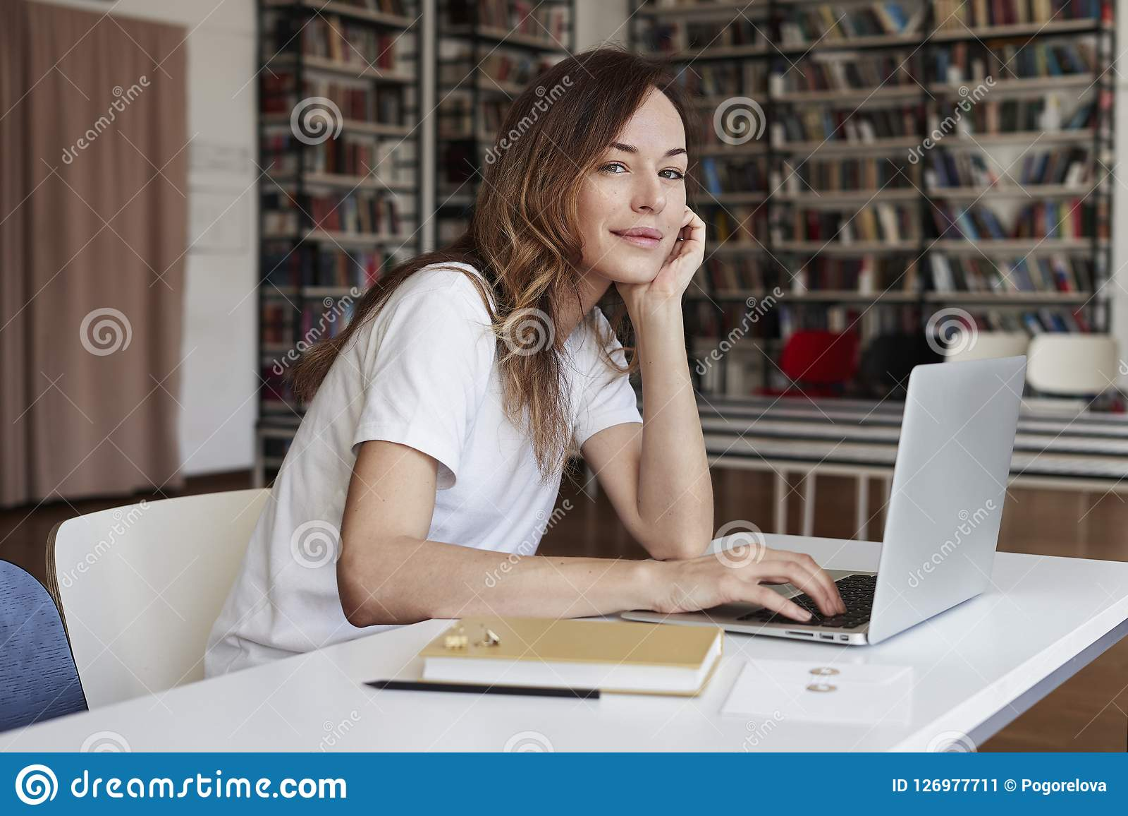 Analista lungo dei capelli della giovane donna che lavora all ufficio dilavoro sul computer portatile, sguardo alla macchina foto