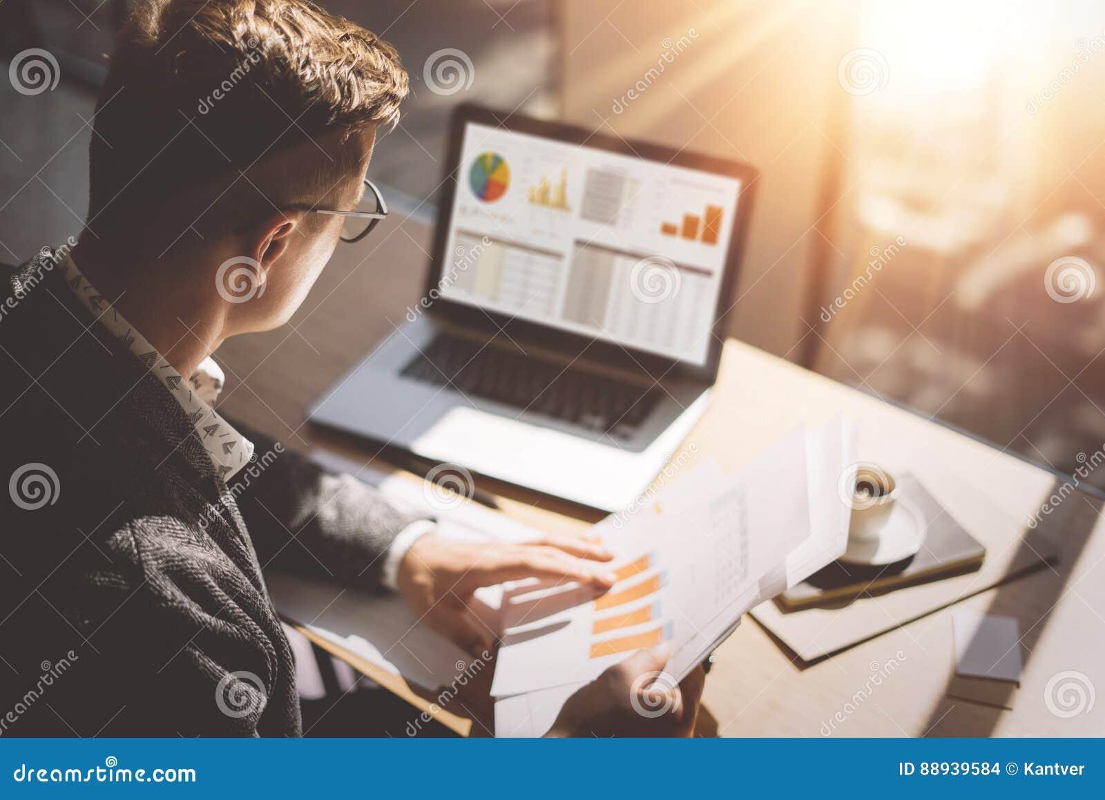 Analista novo do mercado de finança nos monóculos que trabalham no escritório ensolarado no portátil ao sentar-se na tabela de ma