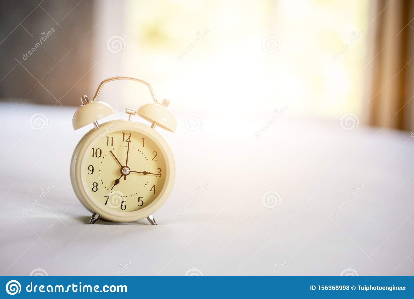 Analog alarm clock on white bed, time in the morning with a bright sunshine