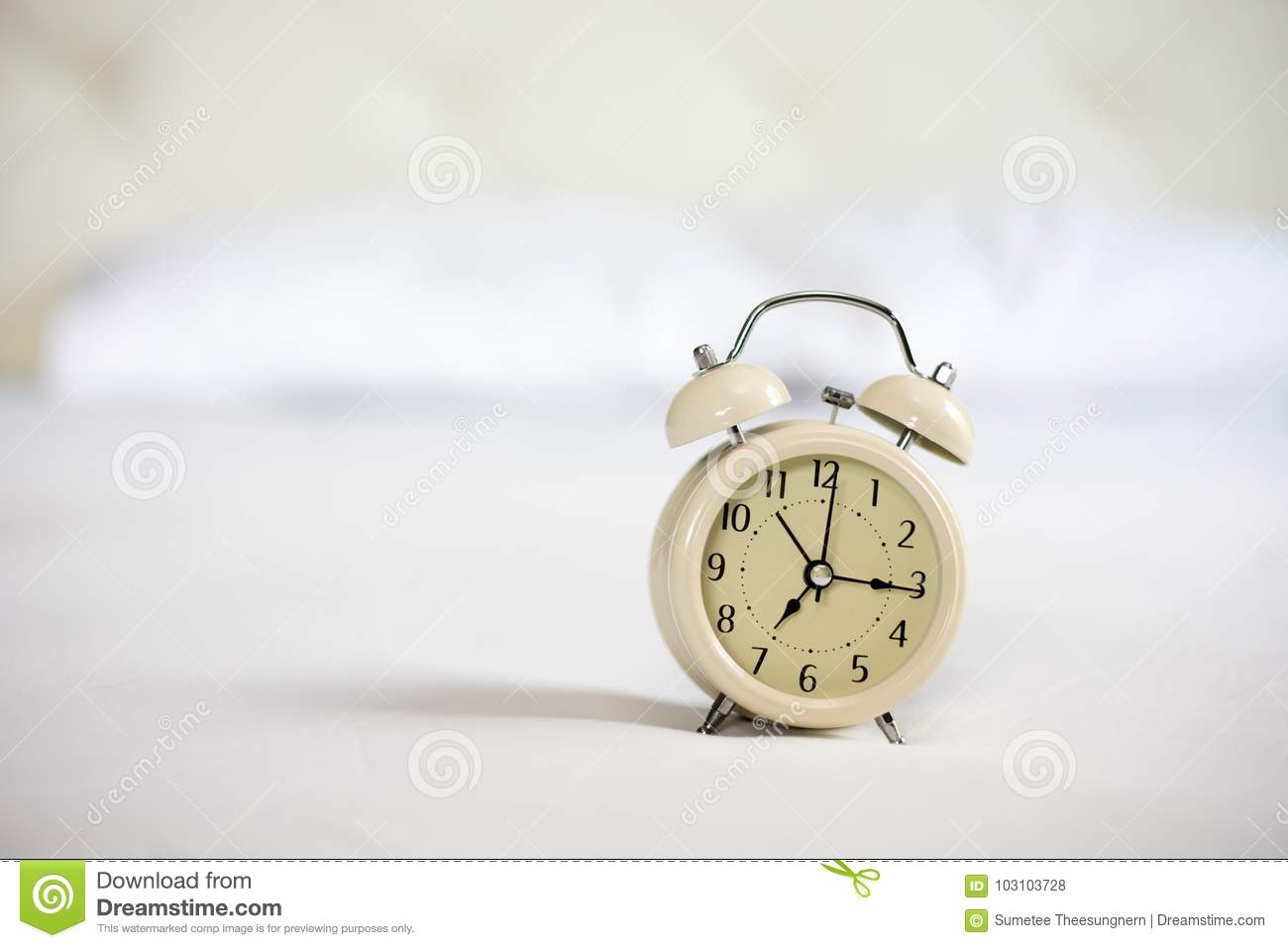 Analog alarm clock on white bed, time in the morning with a brig