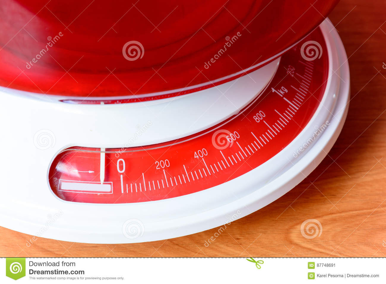 Analog red kitchen scales on the wooden table