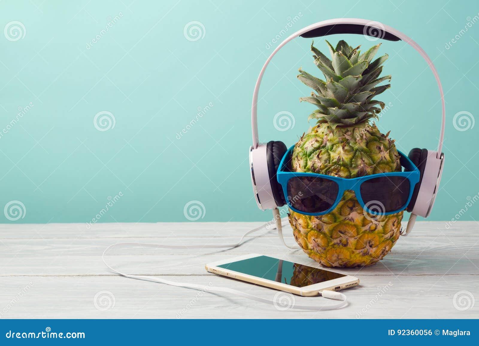 Ananas avec des lunettes de soleil, des écouteurs et le téléphone intelligent sur la table en bois au-dessus du fond en bon état