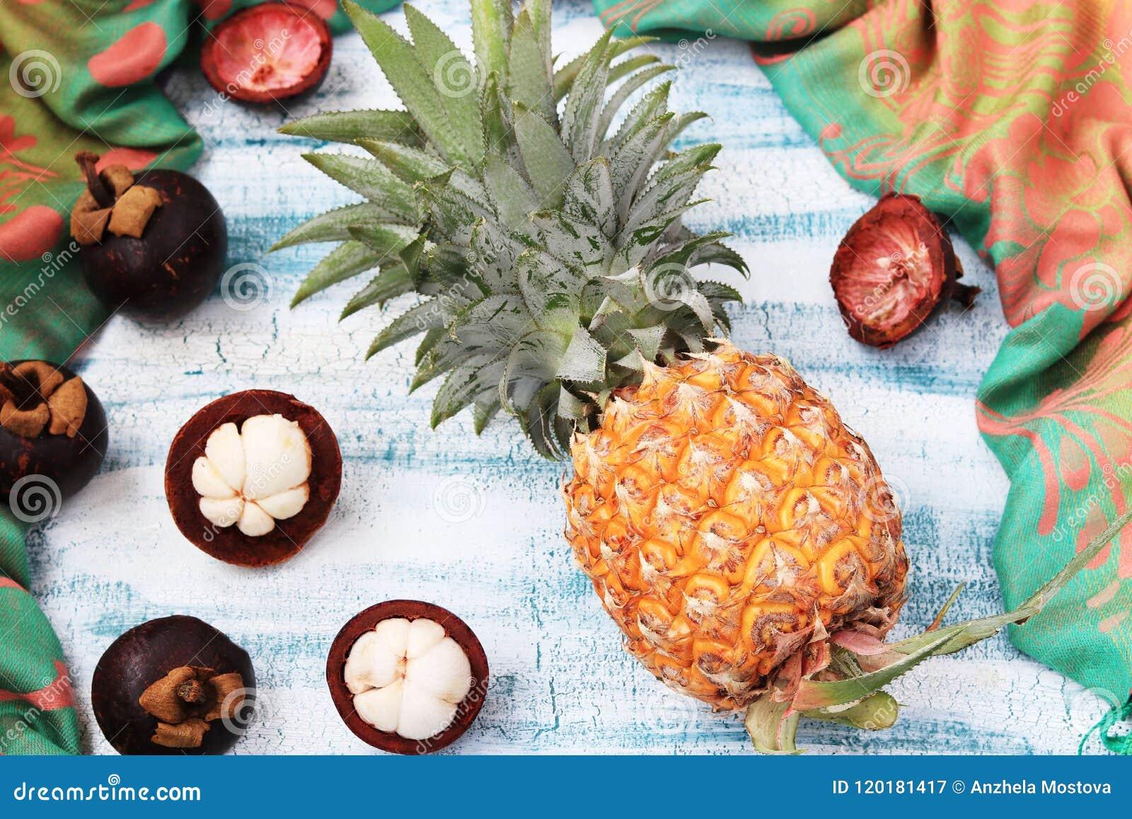 Ananas e mangostano su un fondo blu, vista superiore