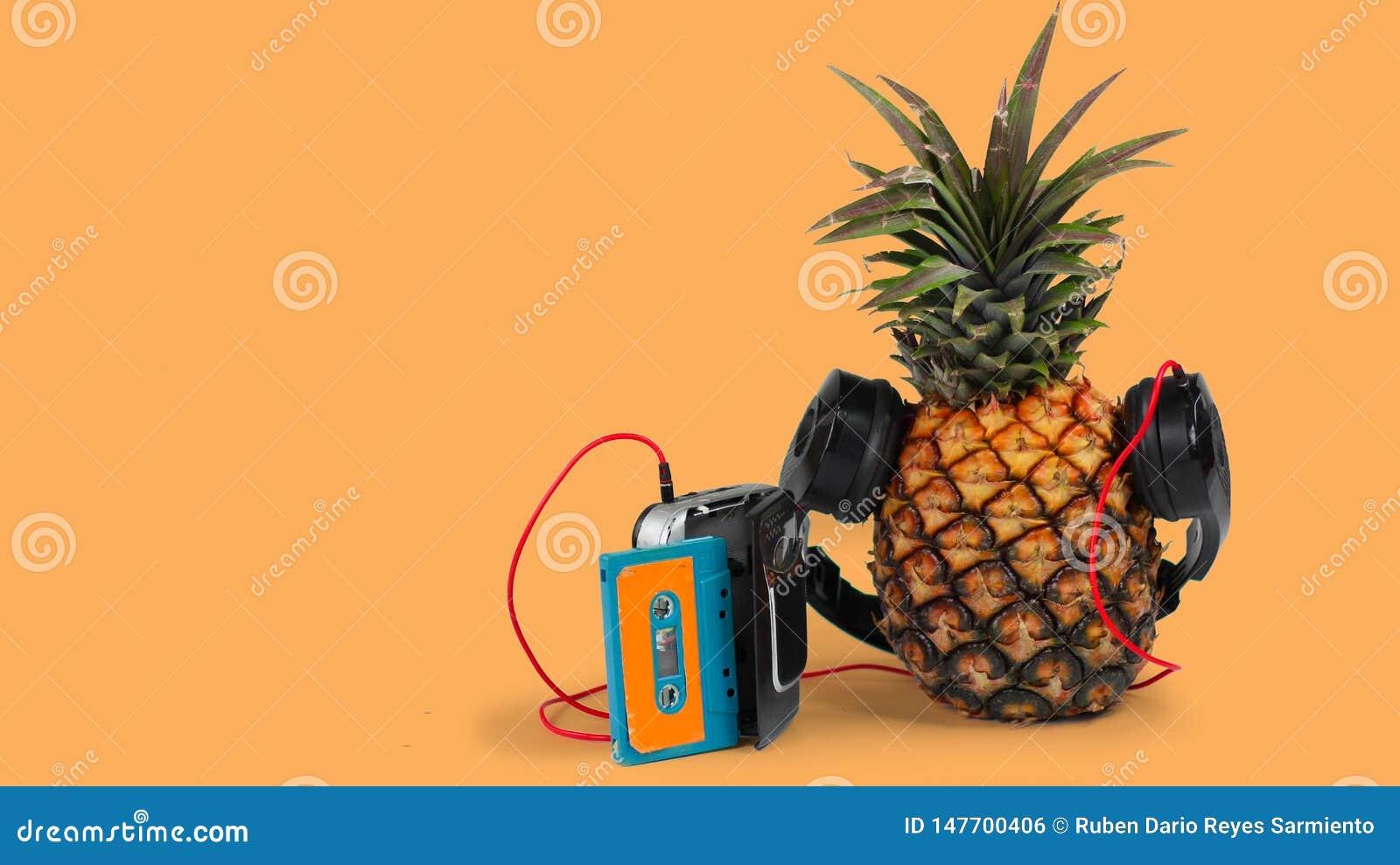Ananas frais avec les écouteurs noirs et le fond orange de wlakman