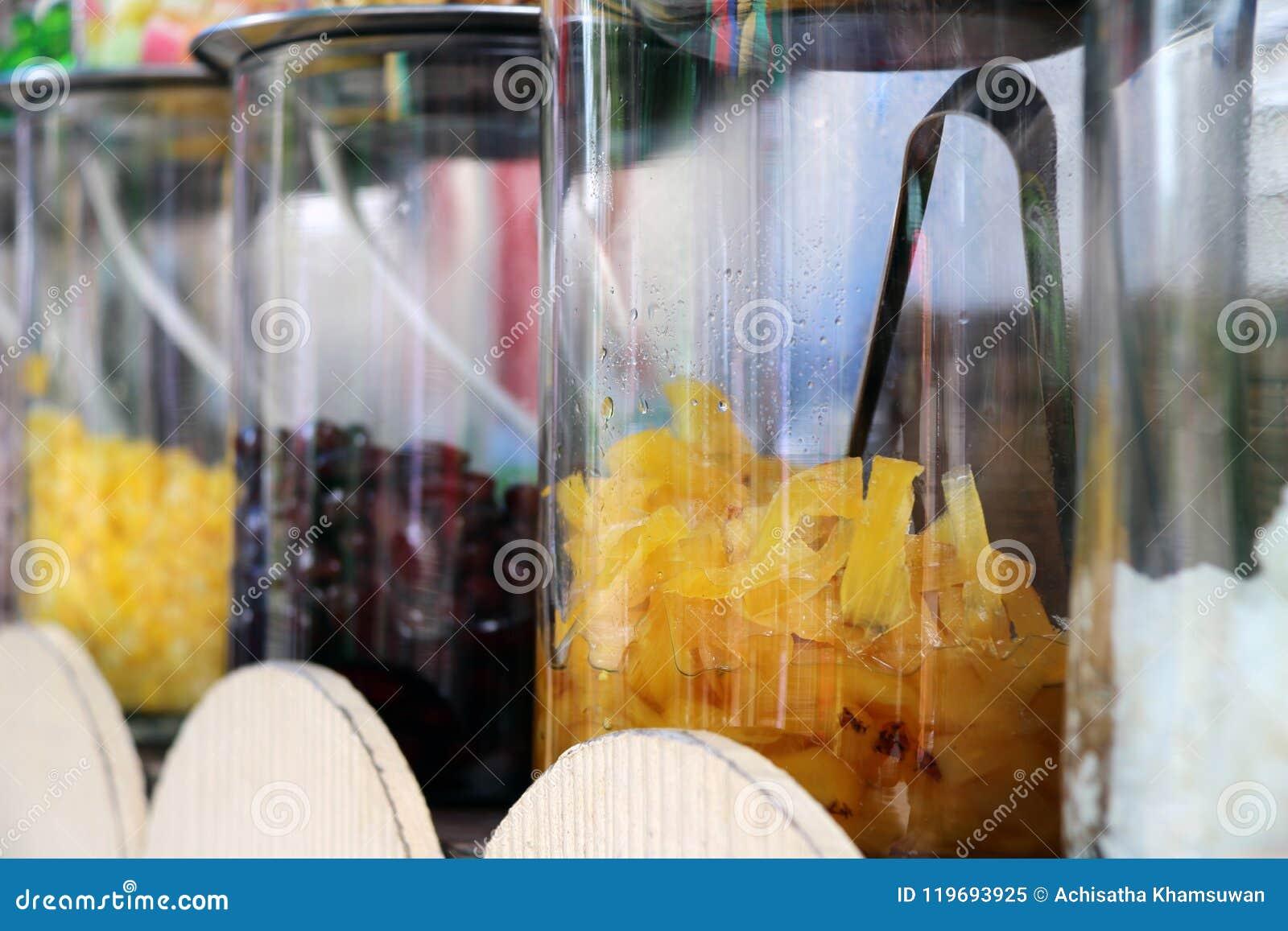 Ananas i sirap i den Glass kruset och raden av socker bär frukt
