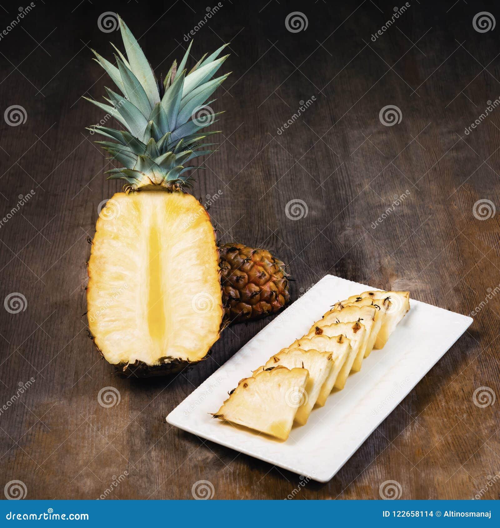 Ananasfrukt klippte halva, fjärdedelen och kilar och visat på den vita plattan och träbakgrund Fyrkantig sammansättning Saftig or