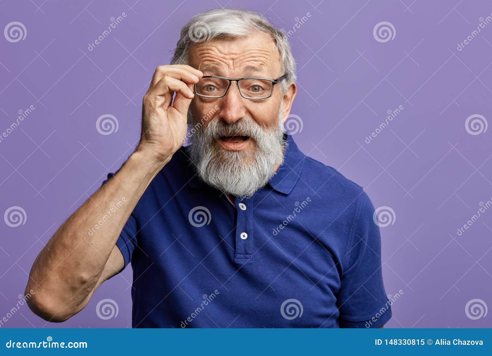 Ancião alegre que olha através dos vidros na câmera