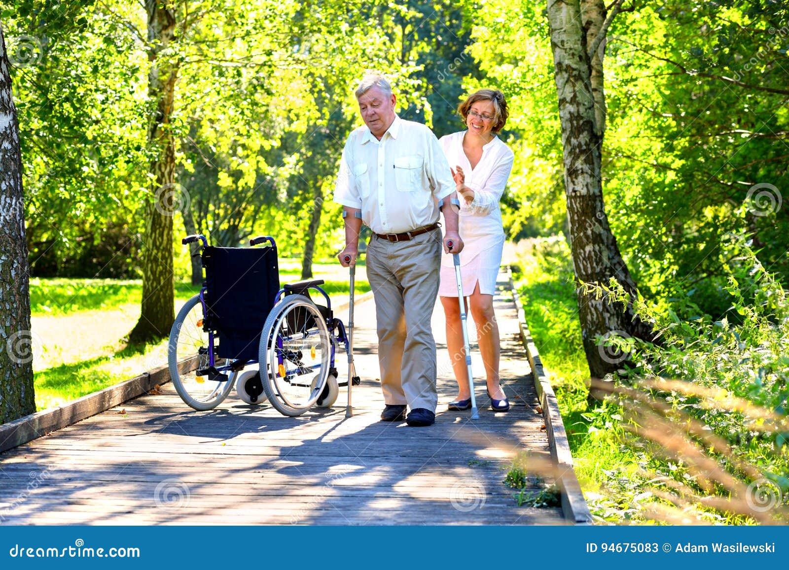 Ancião com muletas e jovem mulher no parque