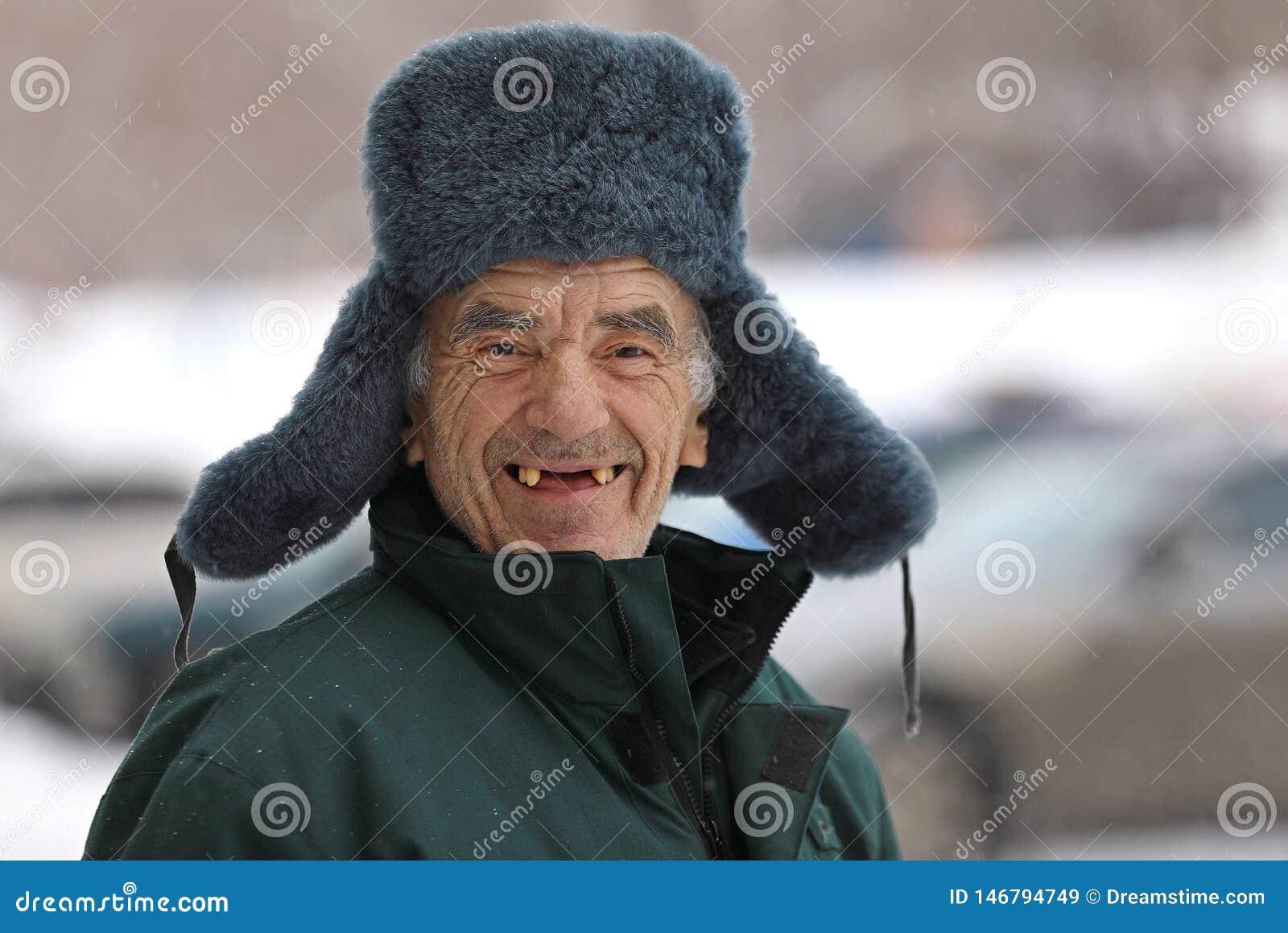 Ancião do russo em sorrisos do chapéu do inverno