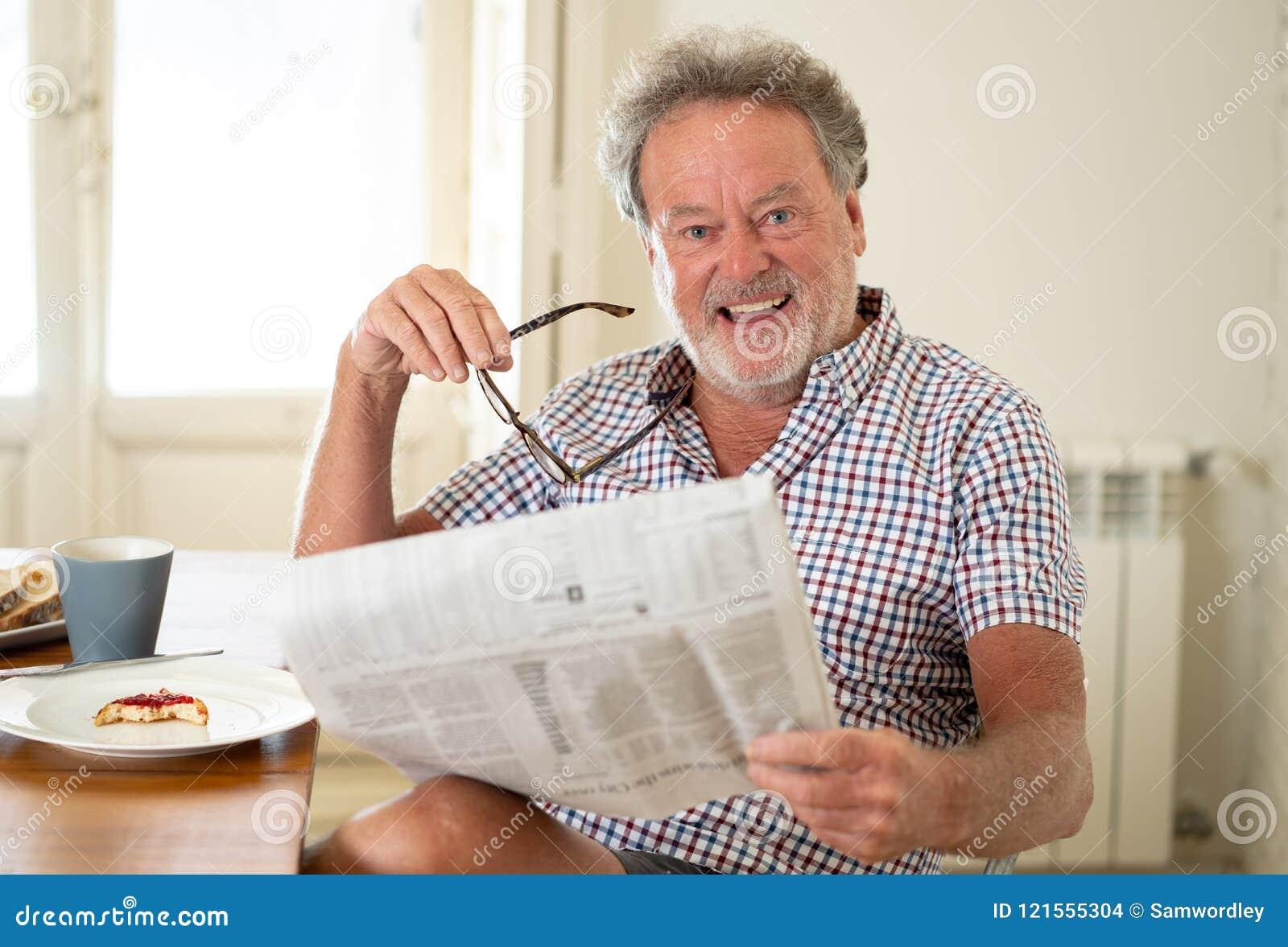 Ancião feliz que lê o jornal ao comer o café da manhã