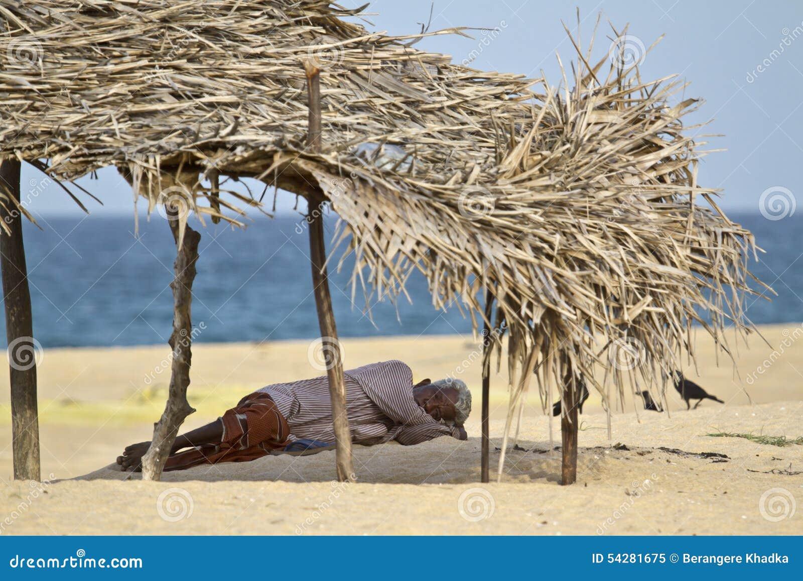 Ancião que descansa na sombra na praia, Batticaloa, Sri Lanka