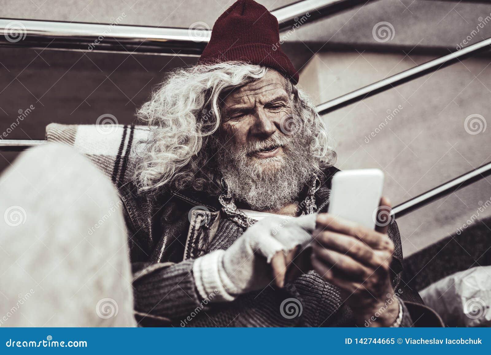 Ancião que olha como os sem abrigo que olham em fotos de sua família na tela