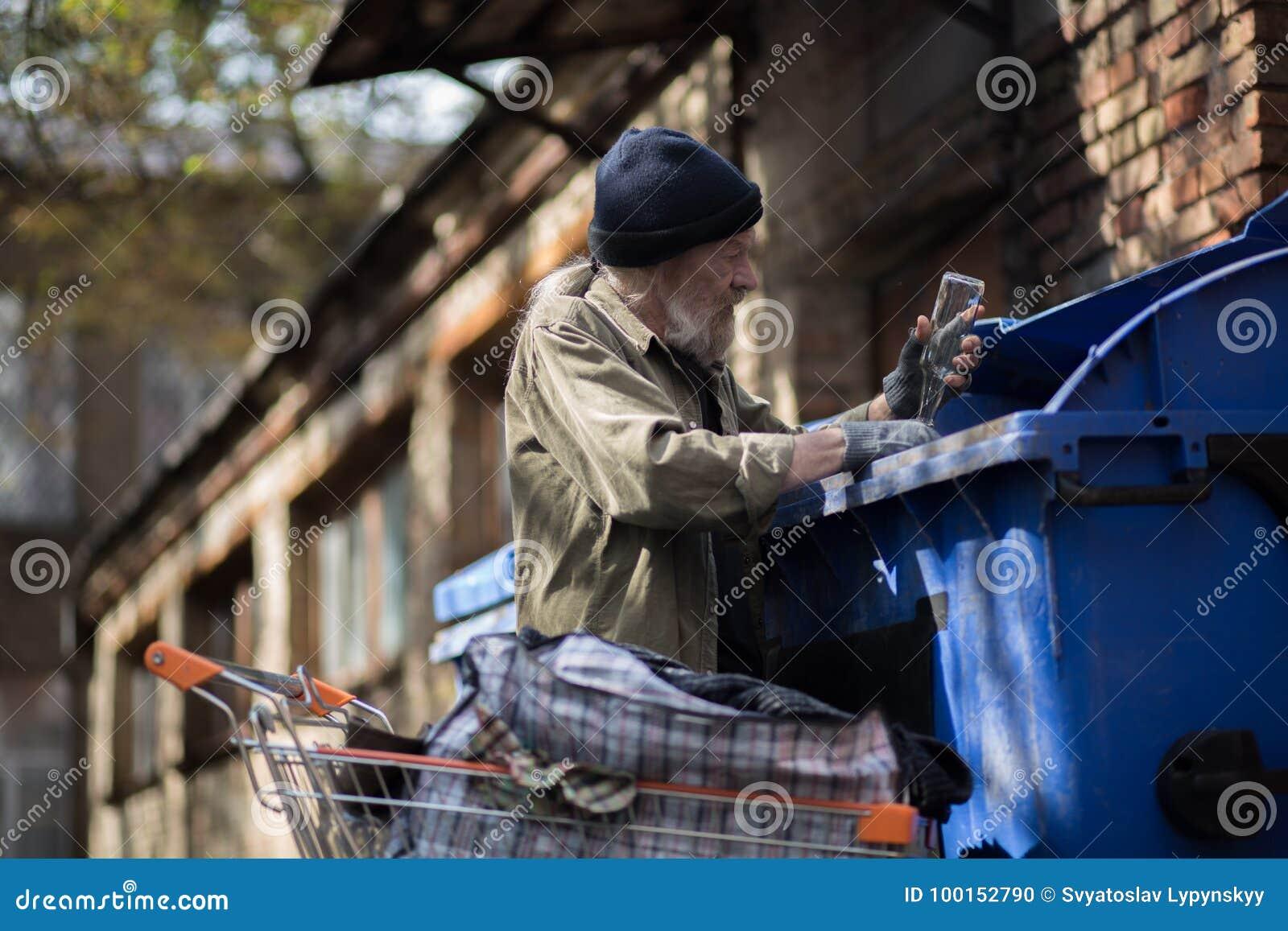 Ancião que recolhe garrafas vazias para ganhar o dinheiro