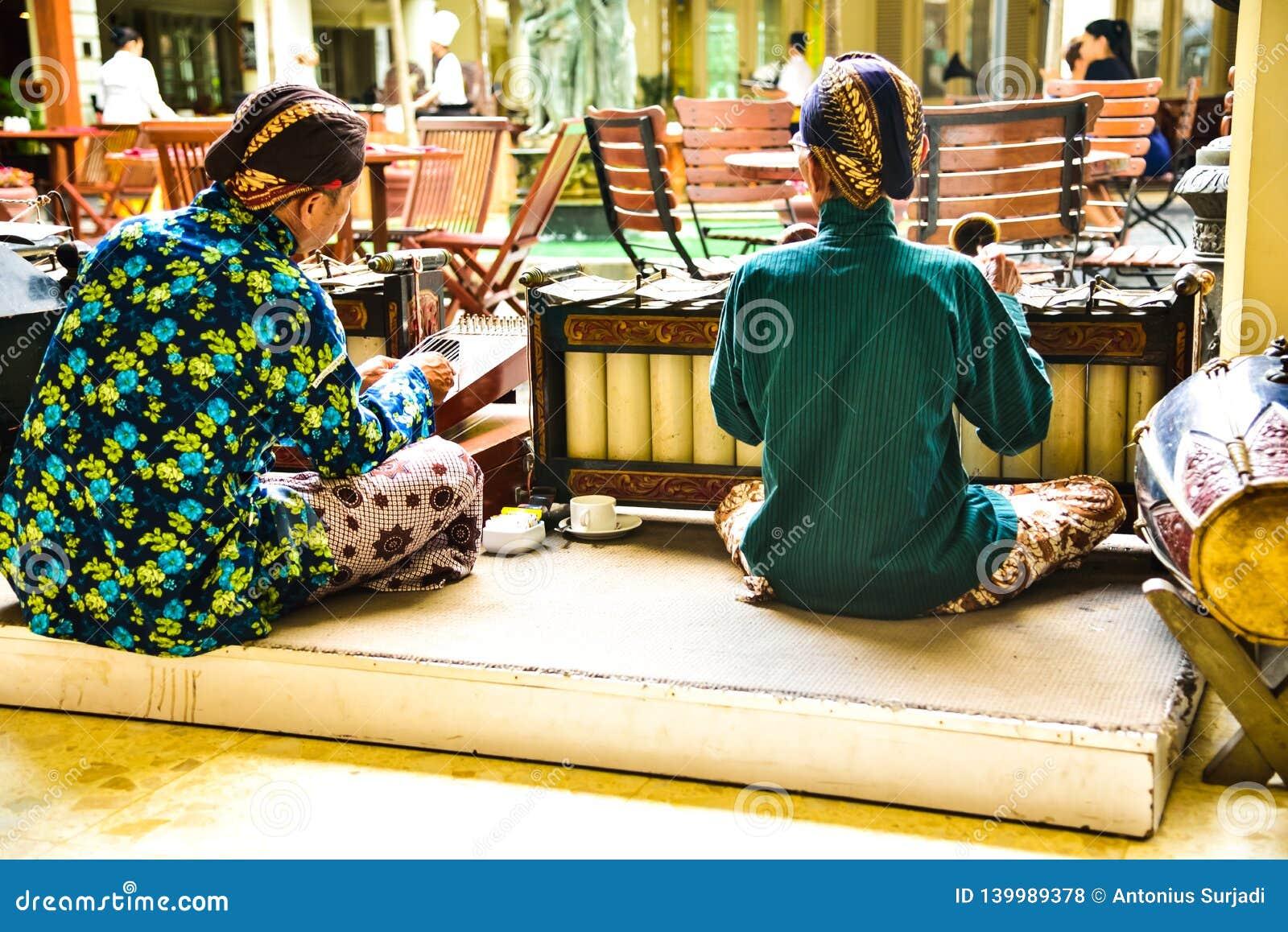 Anciões que vestem o uniforme tradicional que joga com os instrumentos de música velhos e antigos