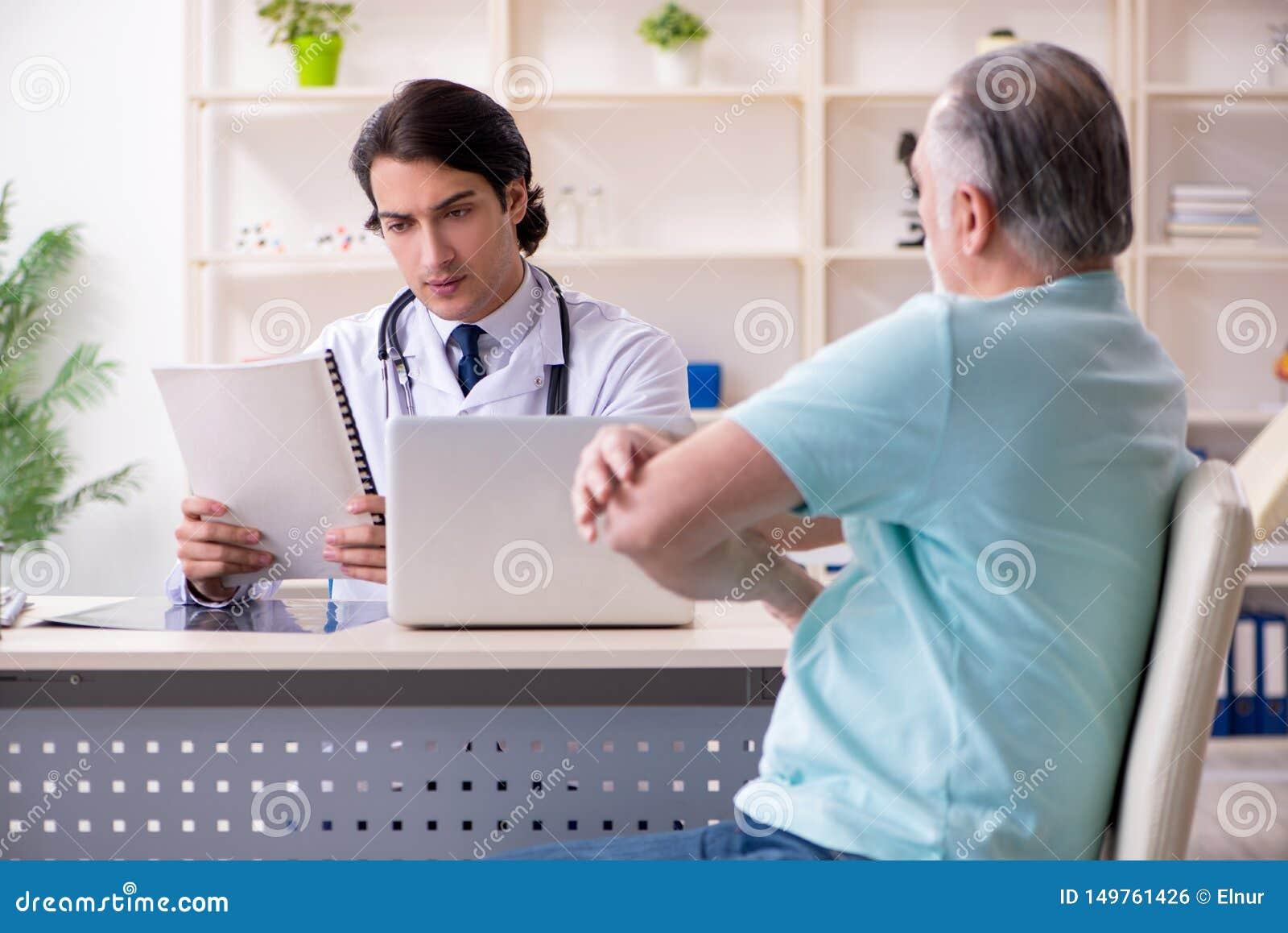 Anci?o que visita o doutor masculino novo
