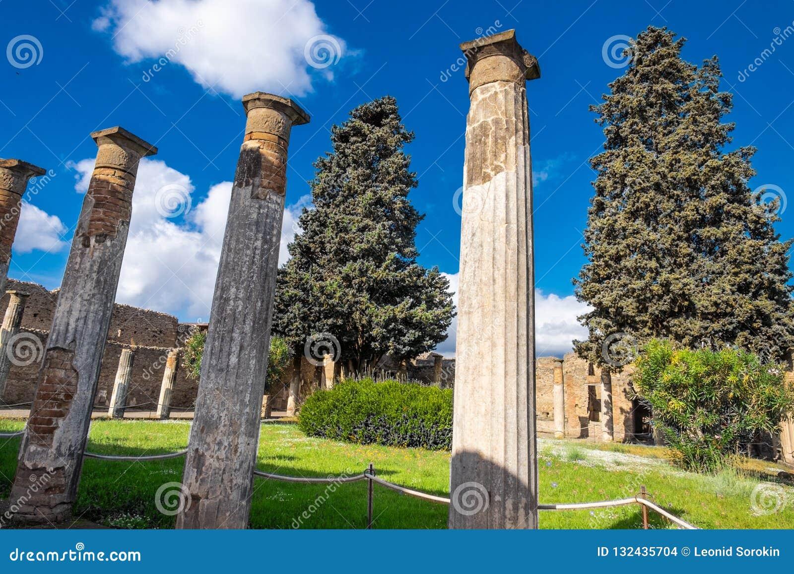 Ancient columns on the garden on Villa in Pompeii, destroyed city