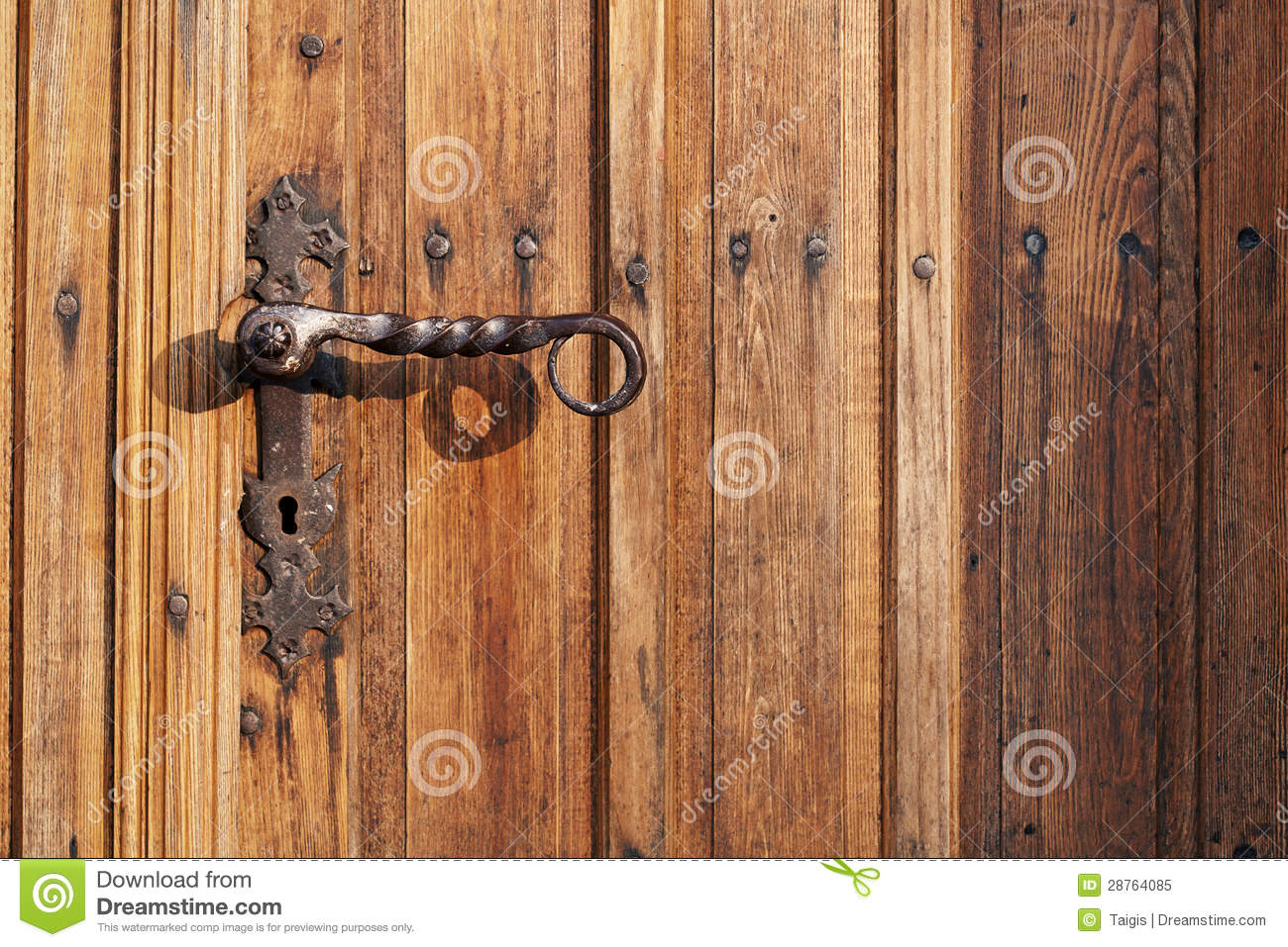 Ancient rusty church door handle on brown old wooden door.
