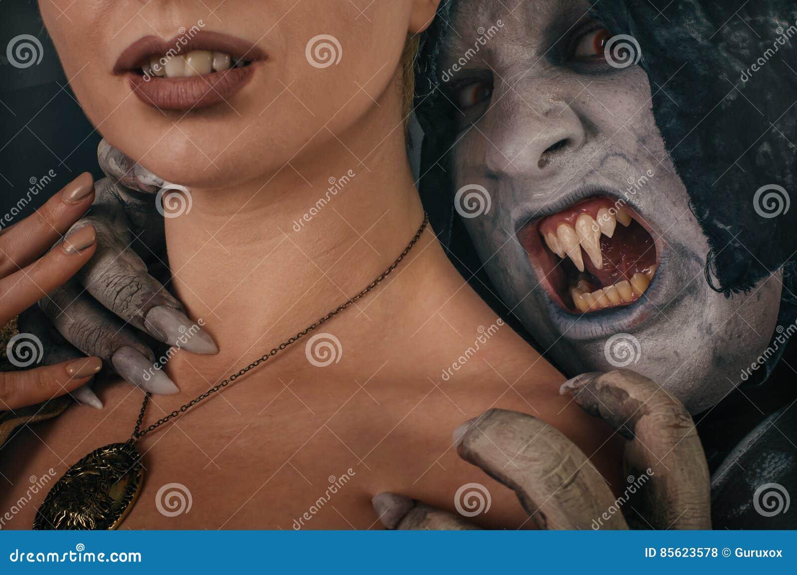 Ancient monster vampire demon bites a woman neck. Halloween fantasy