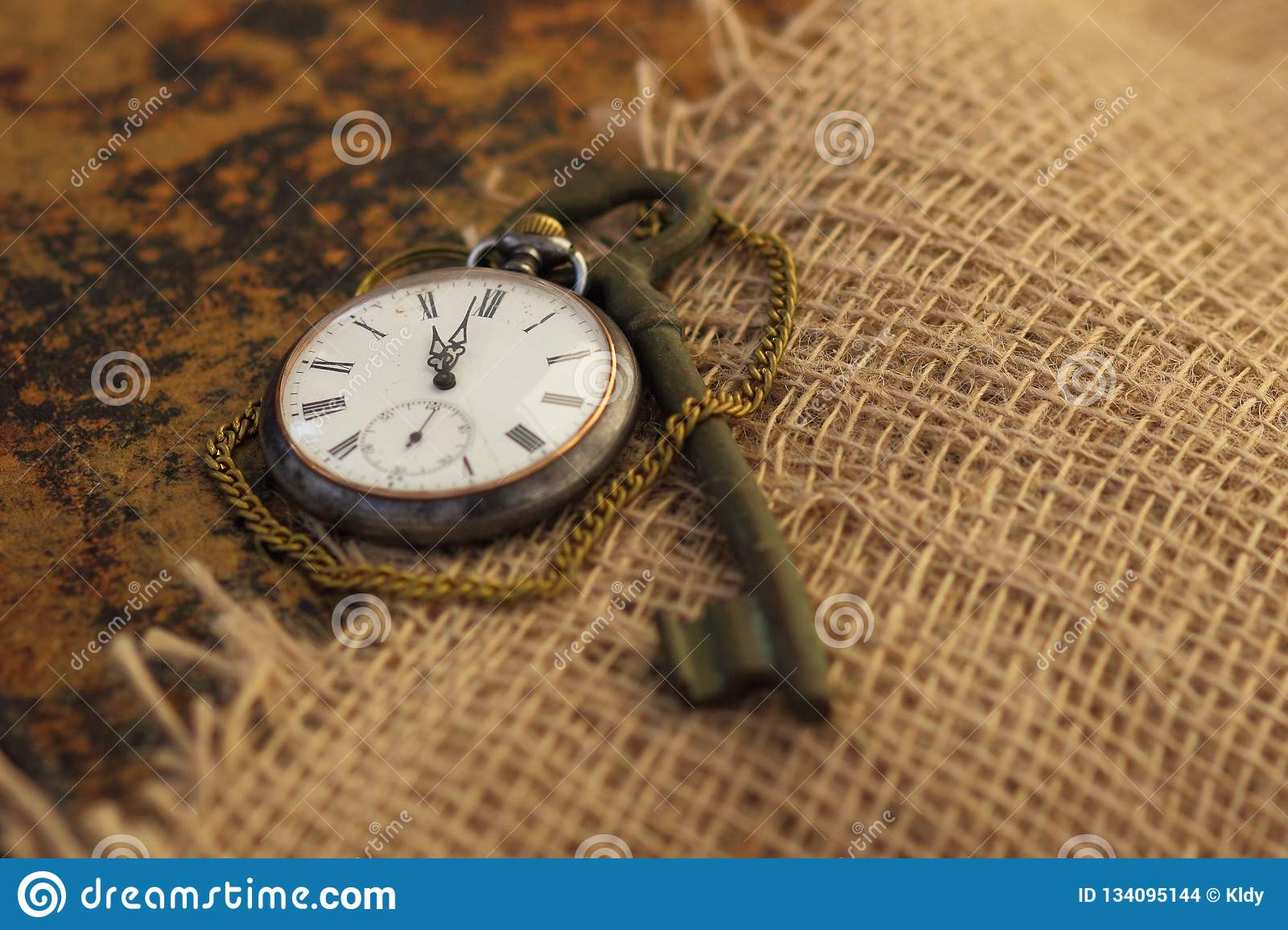 Ancient pocket watch and key on old folio half-covered with old sackcloth. Time passing concept. Knowledge eternity concept